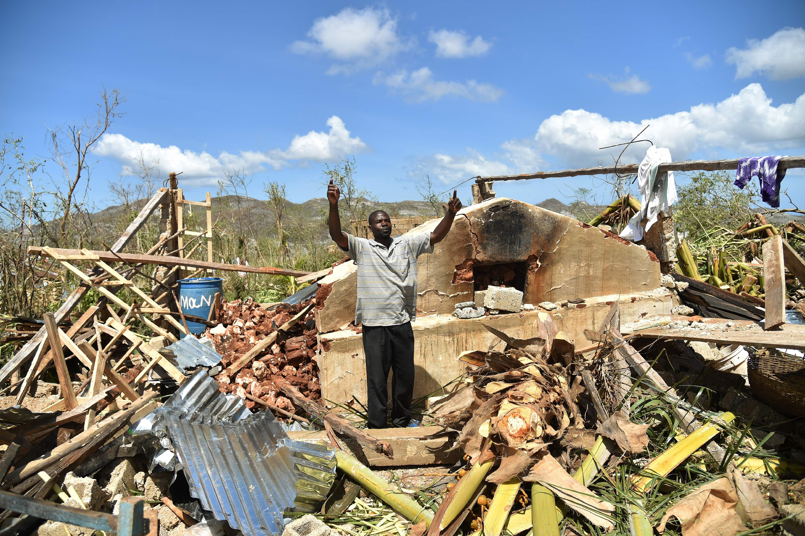 A man gestures while standing in his house damaged in hurricane Matthew, in Deson, southwest Haiti, on Oct. 7, 2016.
