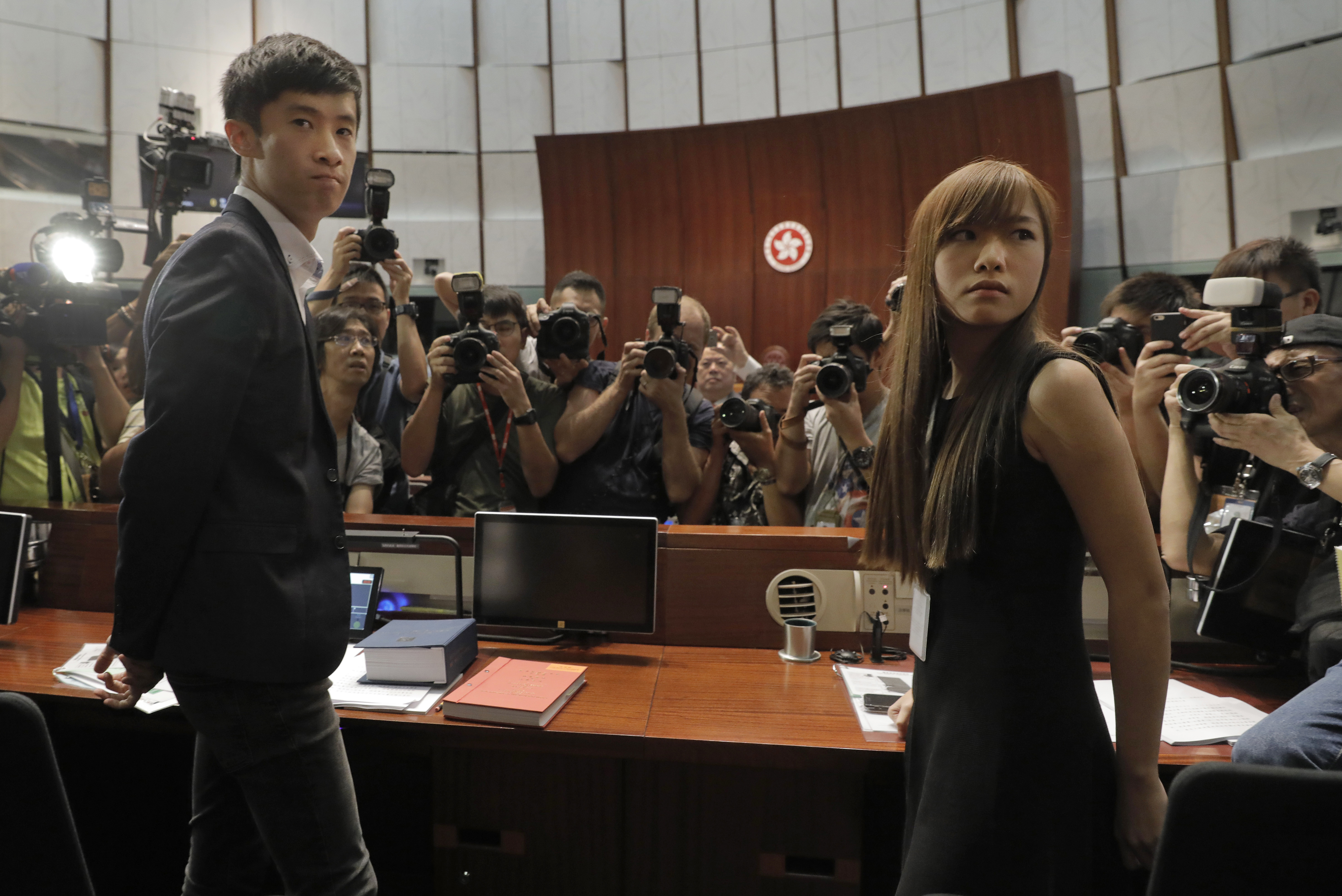 Newly elected Hong Kong lawmakers Yau Wai-ching, right, and Sixtus Leung, left, are surrounded by photographers at legislature council in Hong Kong Wednesday, Oct. 26, 2016. Unruly scenes have gripped Hong Kong's legislature as two newly elected lawmakers defied an order barring them from entering to retake their oaths.