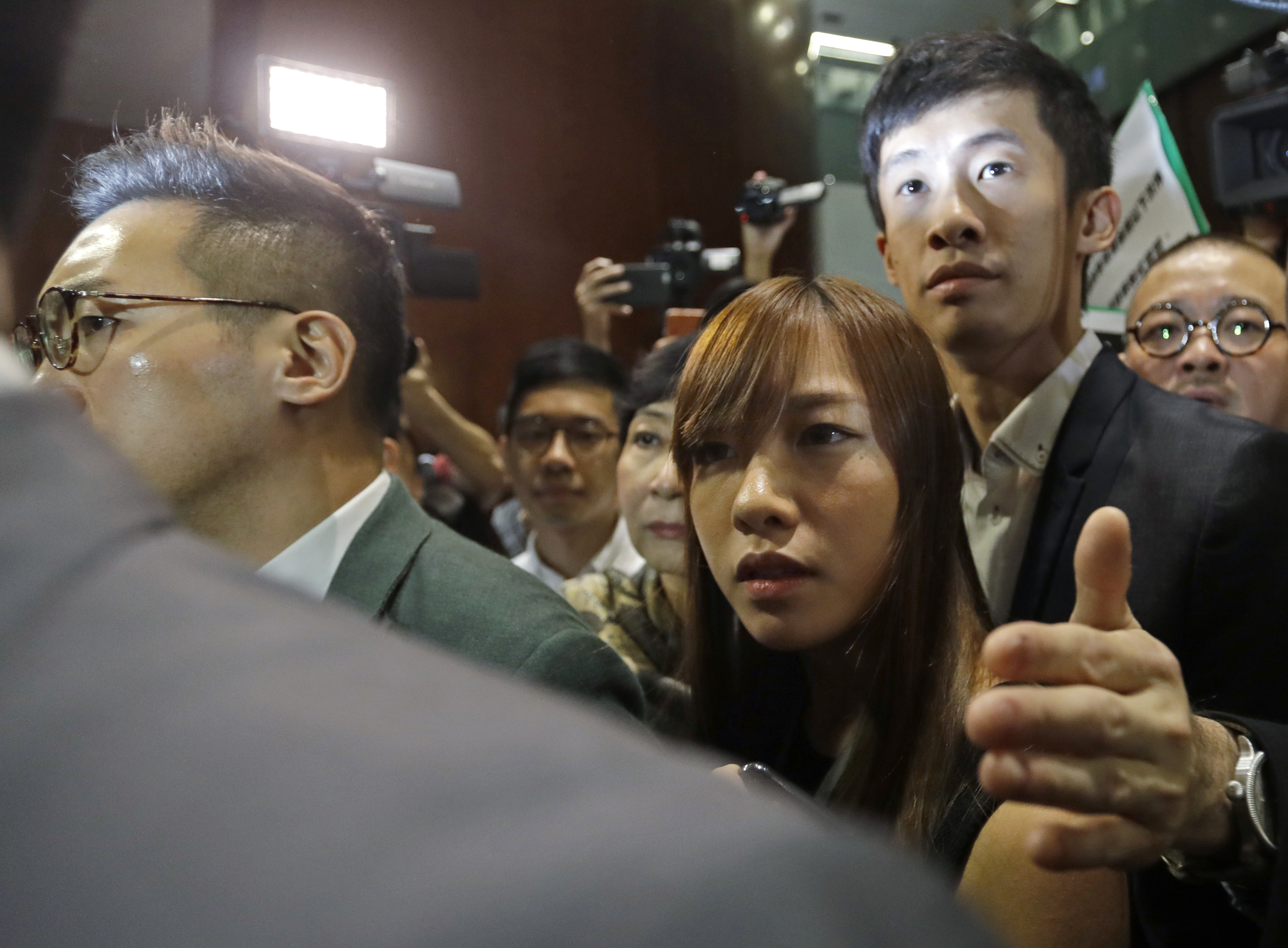 Hong Kong lawmakers Yau Wai-ching, center, and Sixtus Leung, right, are escorted by pan-democrats to enter the legislative chamber in Hong Kong on Oct. 26, 2016. More unruly scenes have erupted at Hong Kong's Legislative Council as the two newly elected lawmakers defied an order barring them from retaking their oaths after being disqualified earlier for swearing allegiance to the  Hong Kong nation