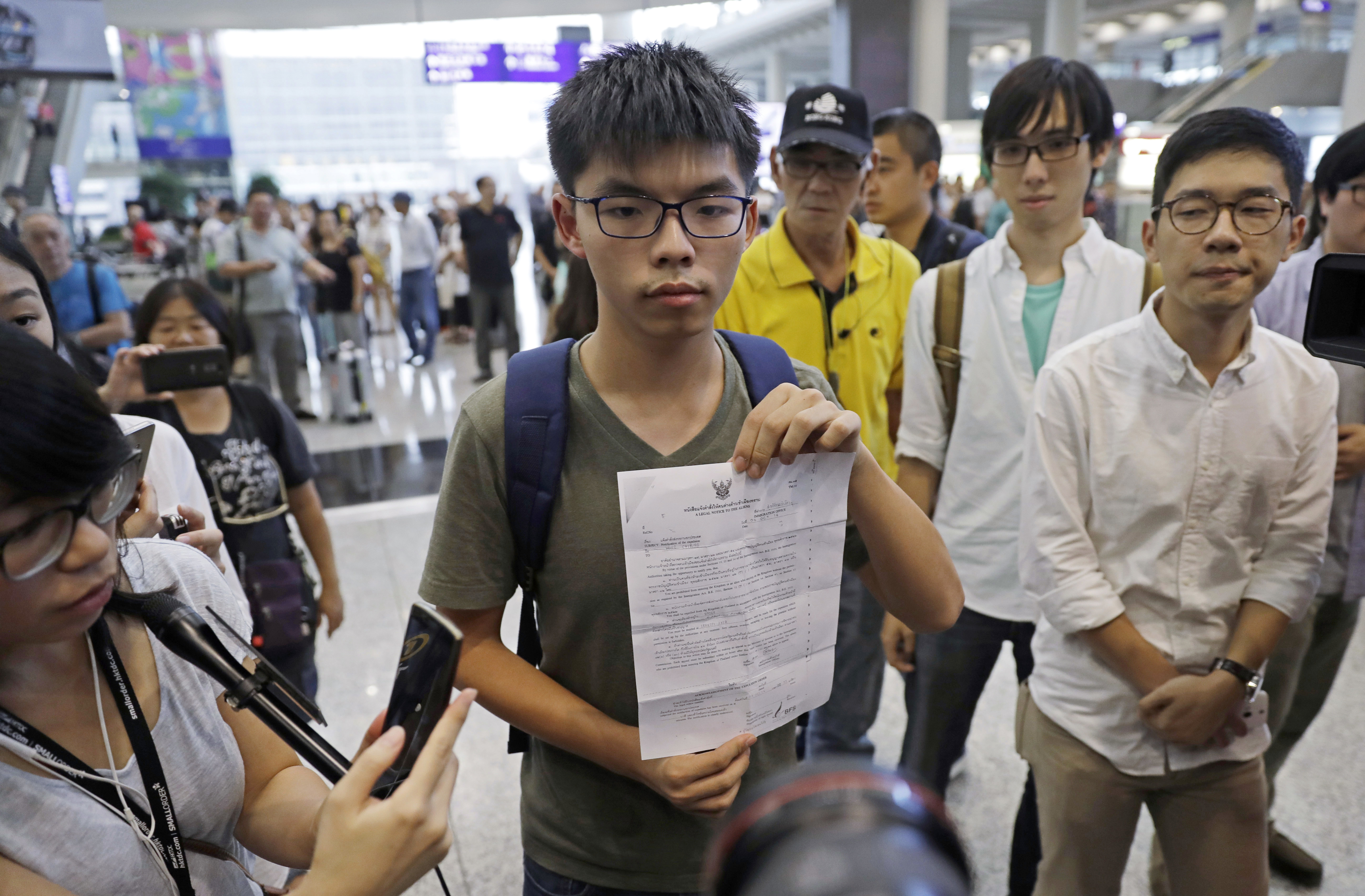 Hong Kong pro-democracy activist Joshua Wong, center, shows a letter from Thailand's immigration office after arriving at Hong Kong airport from Bangkok on Oct. 5, 2016. Thailand stopped the 19-year-old activist from entering the country and sent him back to Hong Kong, officials said, in a move supporters suspected was triggered by pressure from Beijing