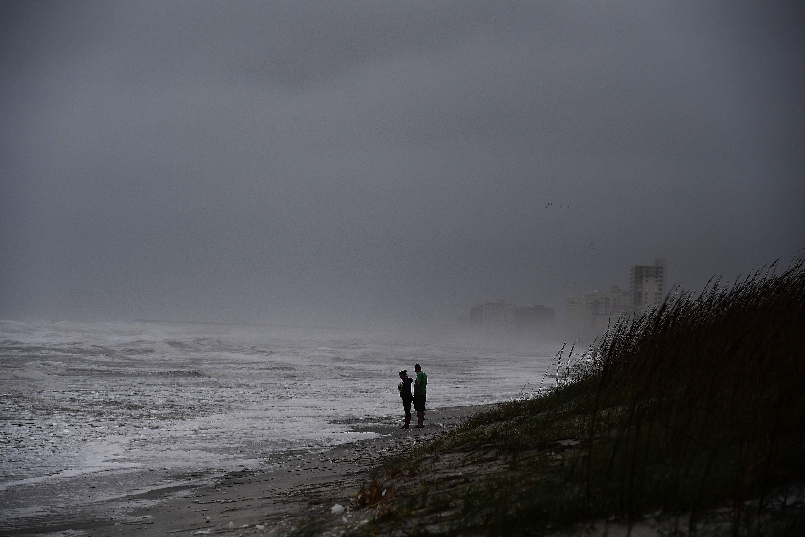 Local residents watch waves at the Atlantic Beach in Jacksonville, Fla., on Oct. 6, 2016.