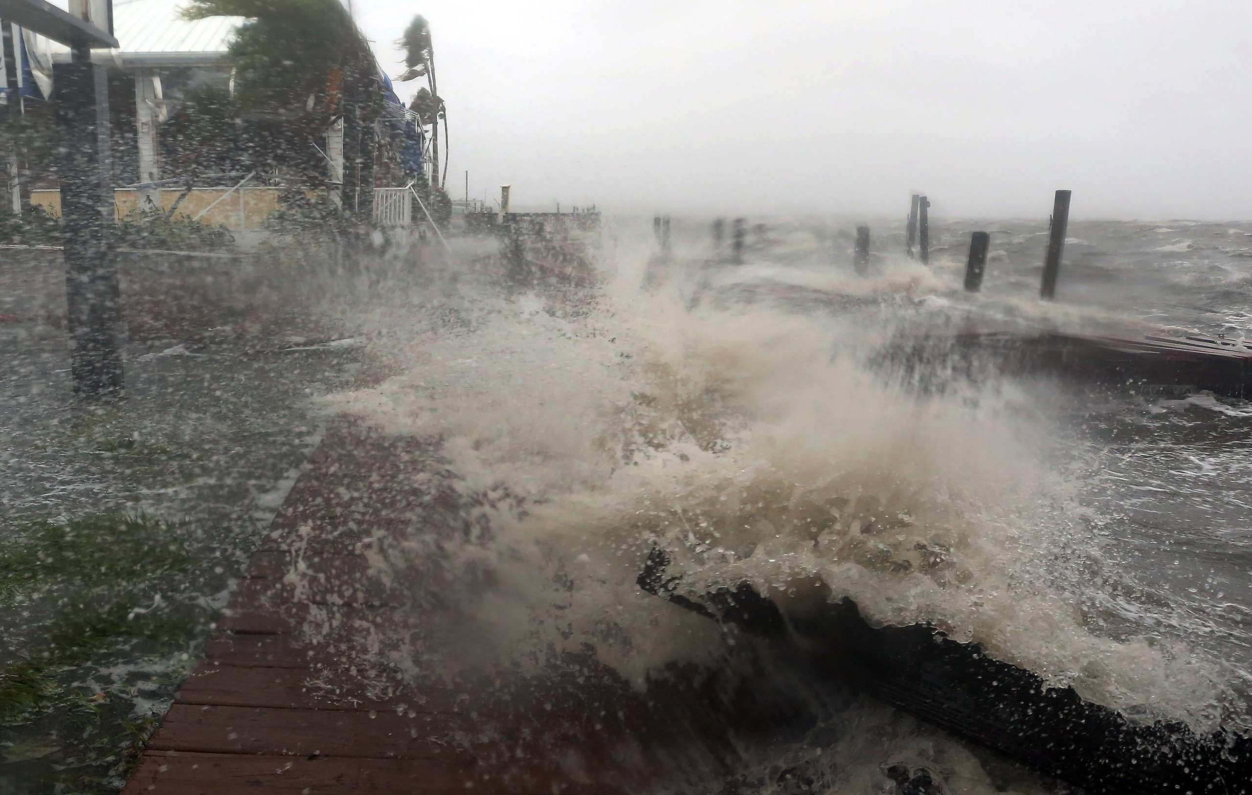 Surf from the Banana River crashes up on a dock at Sunset Grill in Cocoa Beach, Fla., as Hurricane Matthew hits Florida's east coast, Oct. 7, 2016.