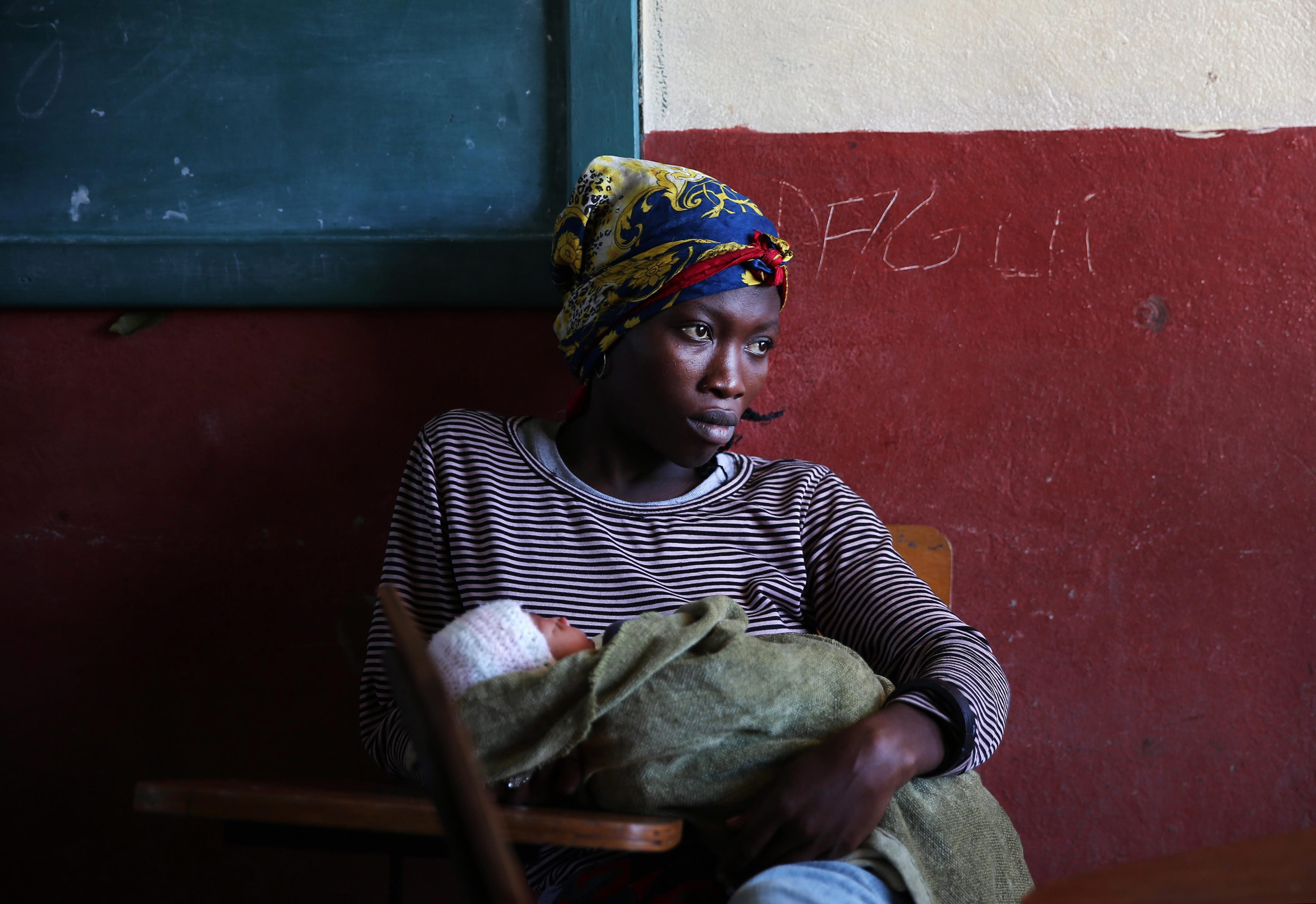 A woman with her baby remains in the shelter of the Lyceum Jean Claudy Muzo in Les Cayes, Haiti, on Oct. 8, 2016.
