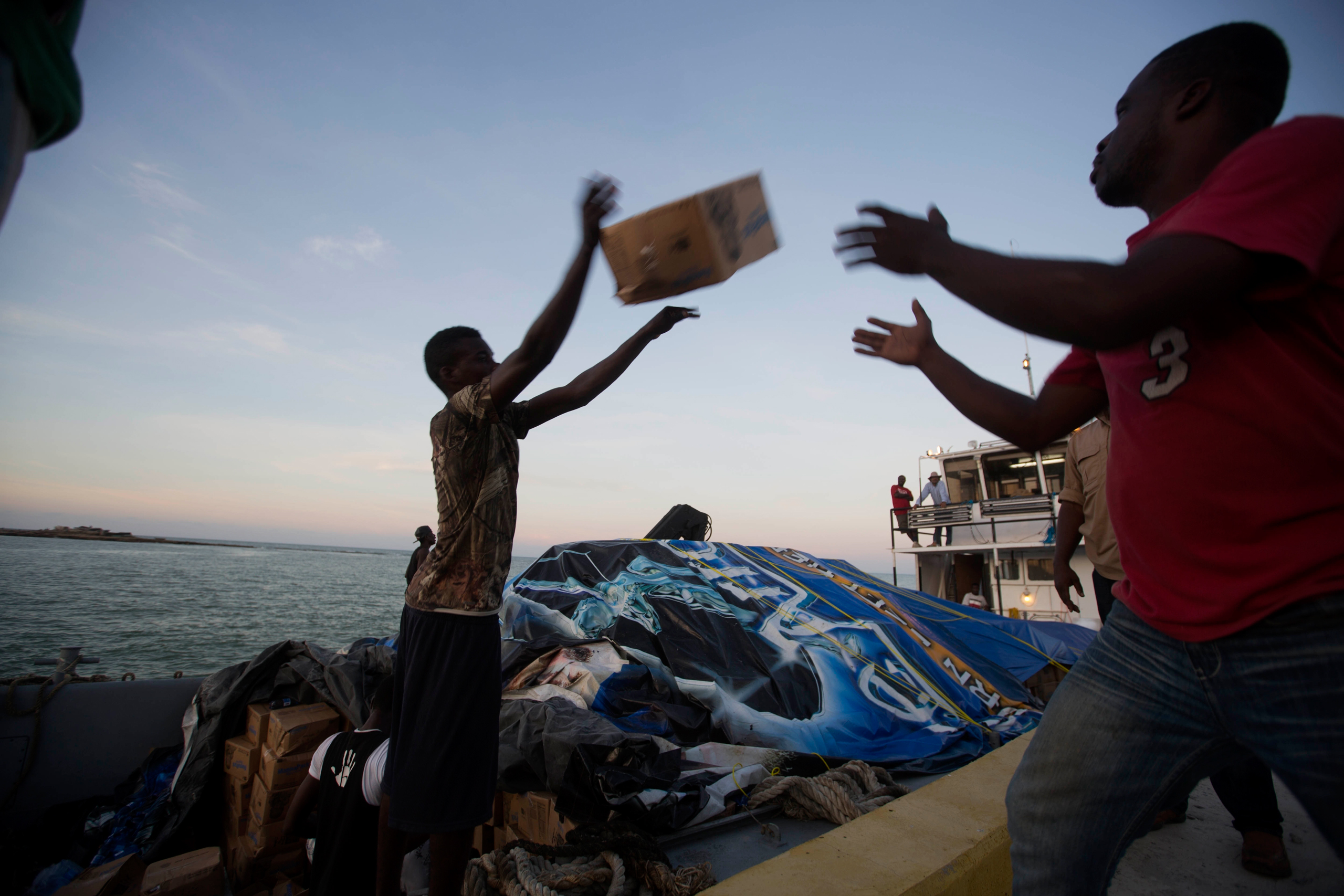 People unload food and water boated in from the  Mission of Hope  charity after Hurricane Matthew swept through Jeremie, Haiti, on Oct. 8, 2016.