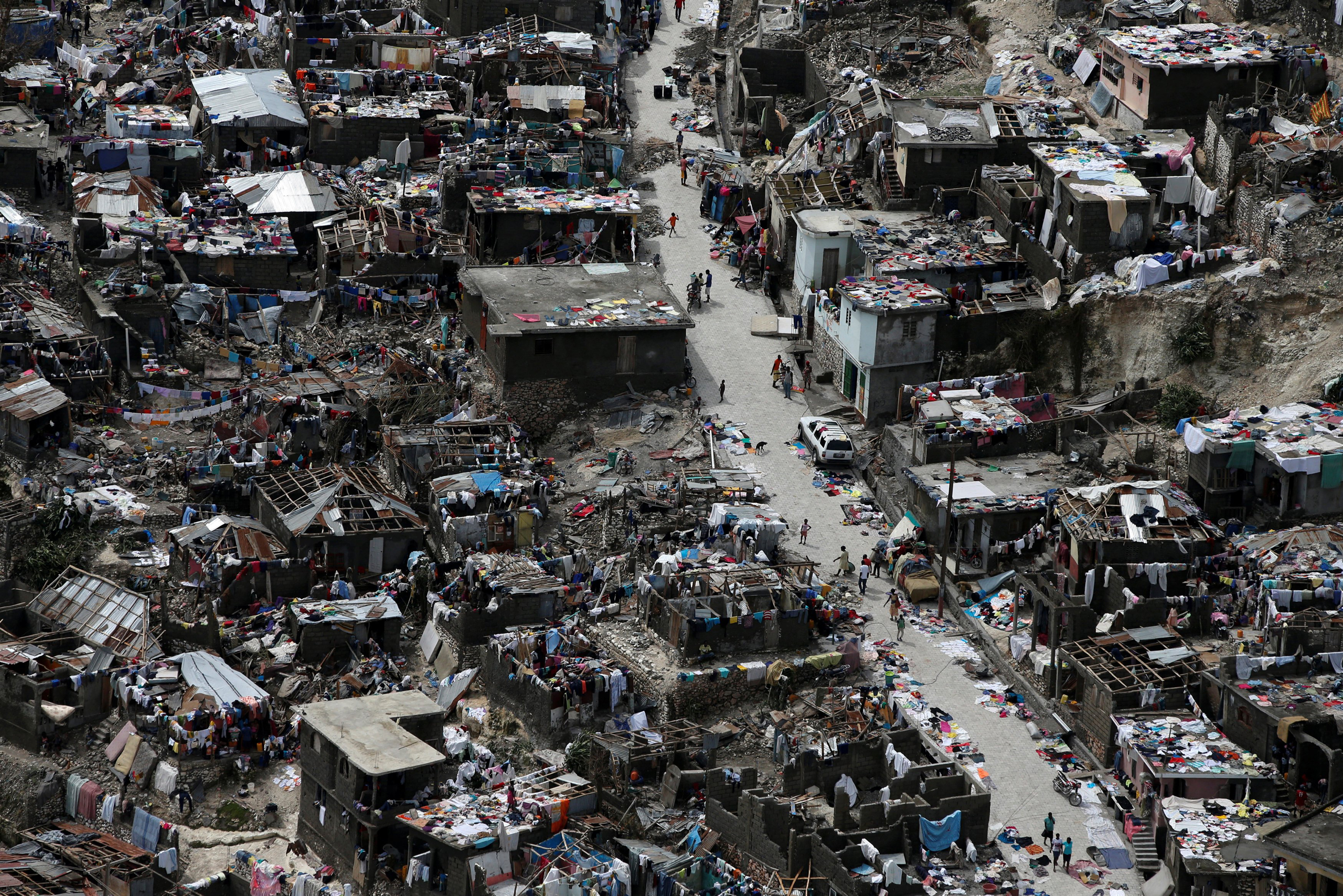 People walk on a street next to destroyed houses after Hurricane Matthew hit Jeremie, Haiti, on Oct. 6, 2016.