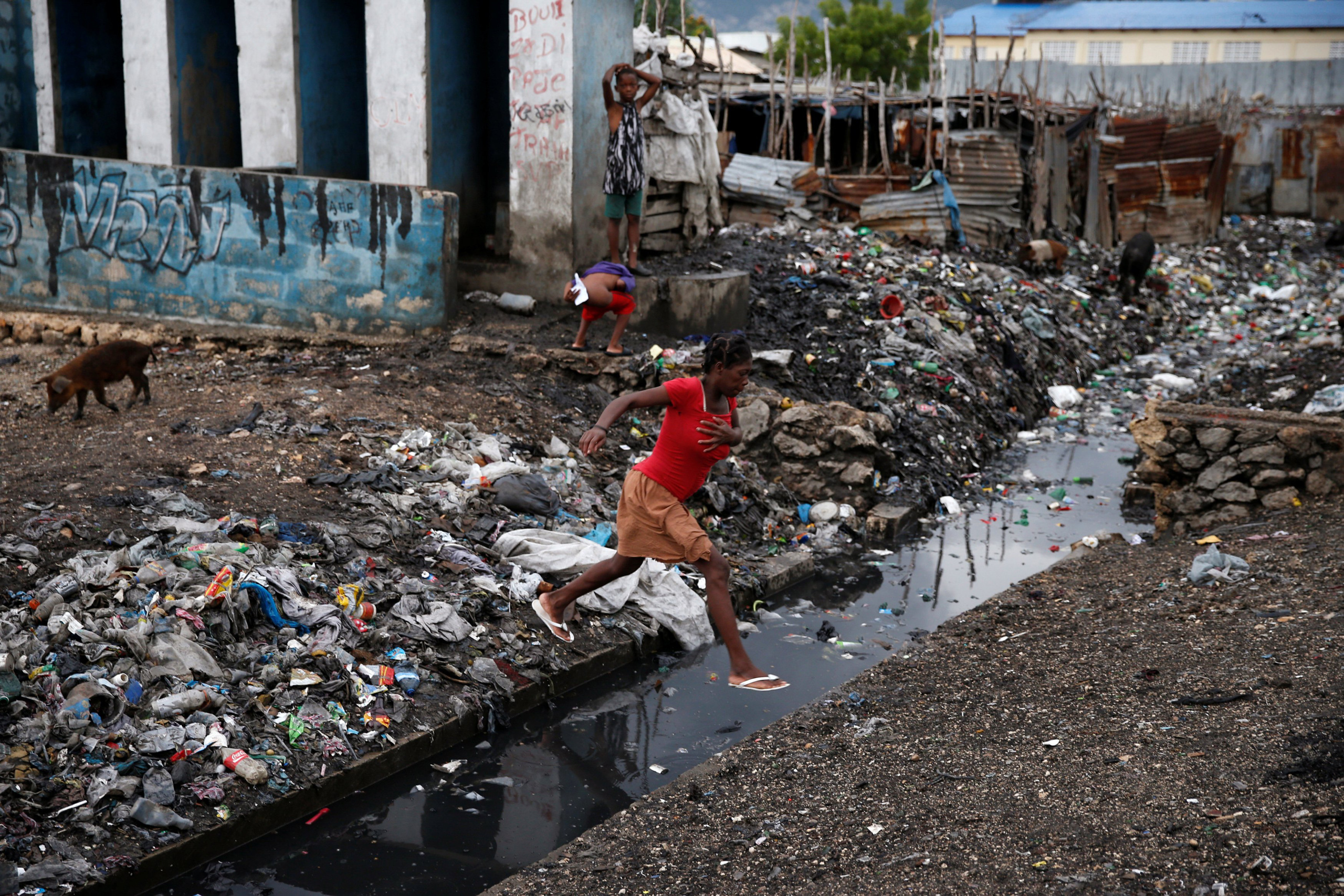 A woman crosses over a water canal after Hurricane Matthew passes Cite-Soleil in Port-au-Prince, Haiti, on Oct. 5, 2016.