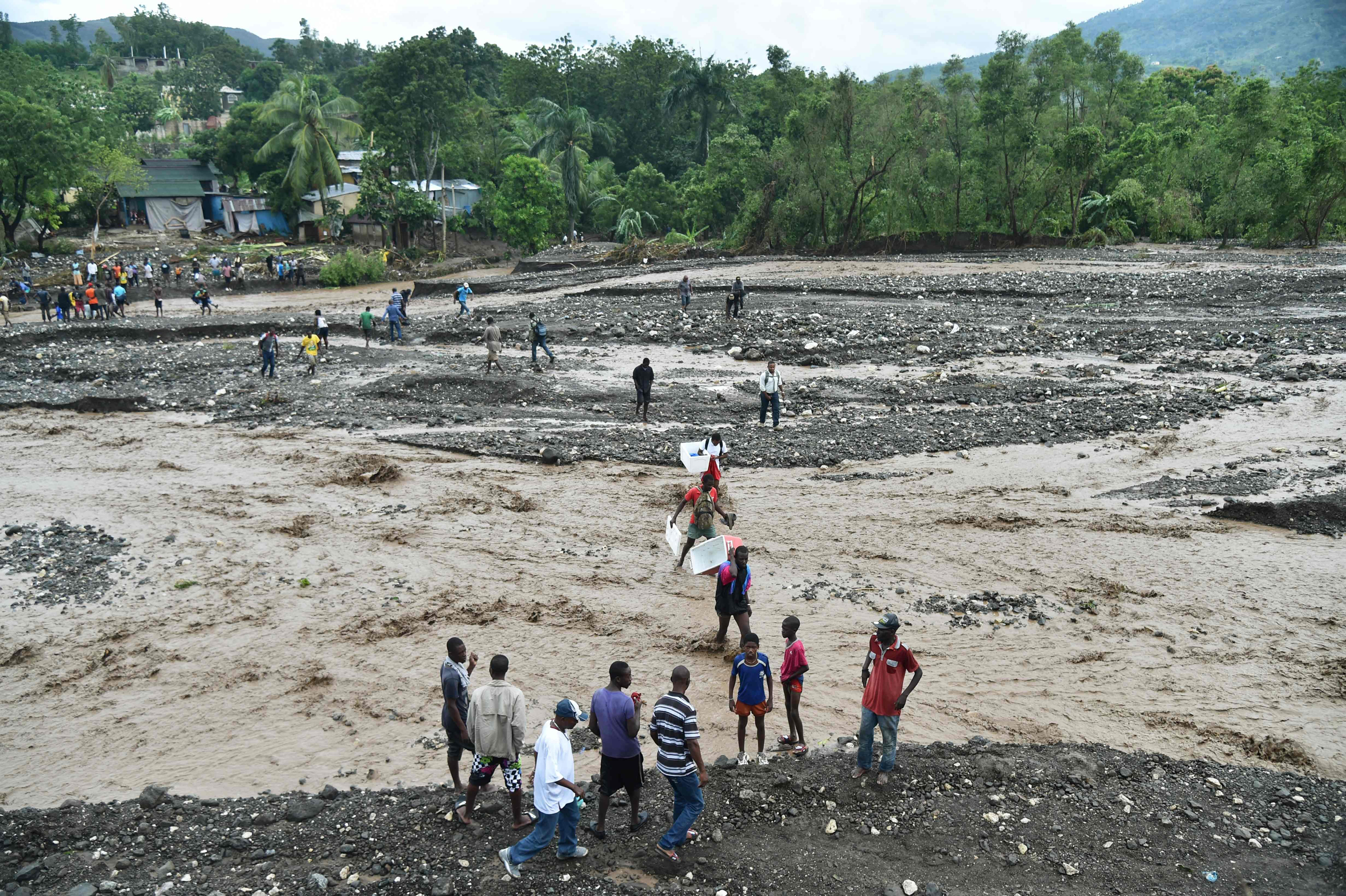 Haitians cross the river La Digue in Petit Goave, where a bridge collapsed during the rains of the Hurricane Matthew, southwest of Port-au-Prince, on Oct. 5, 2016.