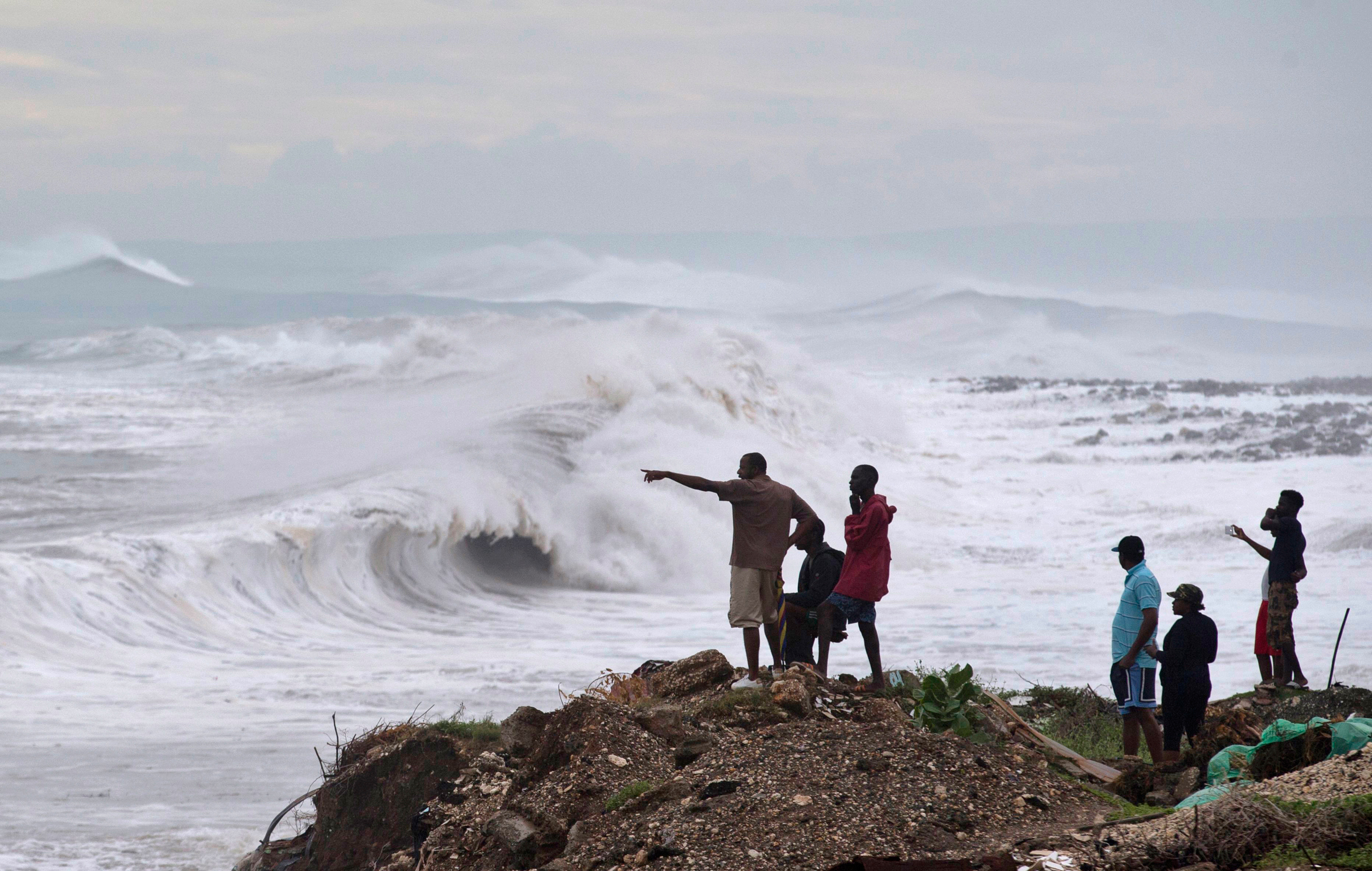 People stand on the coast watching the surf produced by Hurricane Matthew, on the outskirts of Kingston, Jamaica, on Oct. 3, 2016.