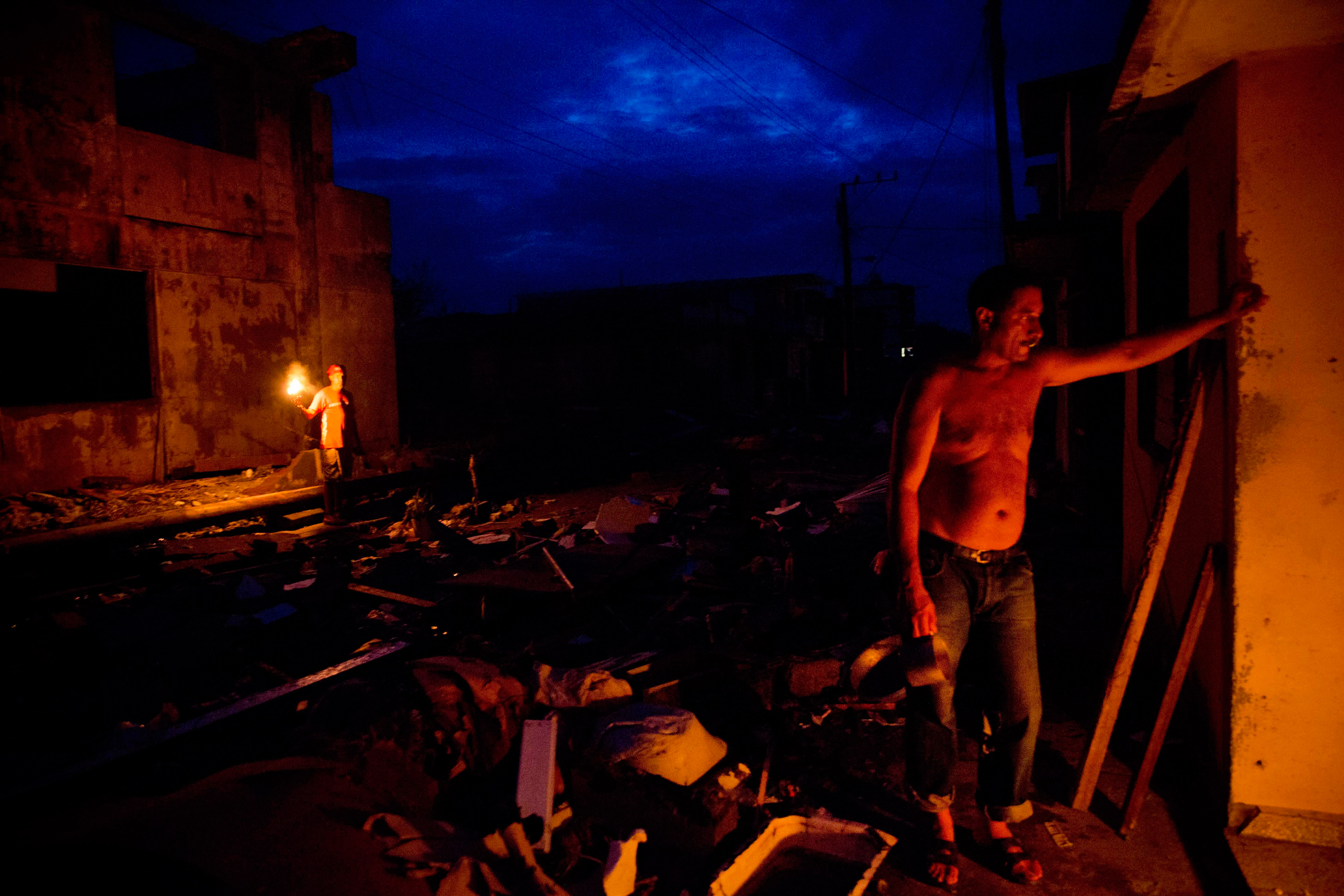 Jorge Luis Azahares waits for his wife to arrive with food amid the ruins of his home destroyed by Hurricane Matthew in Baracoa, Cuba, on Oct. 6, 2016.