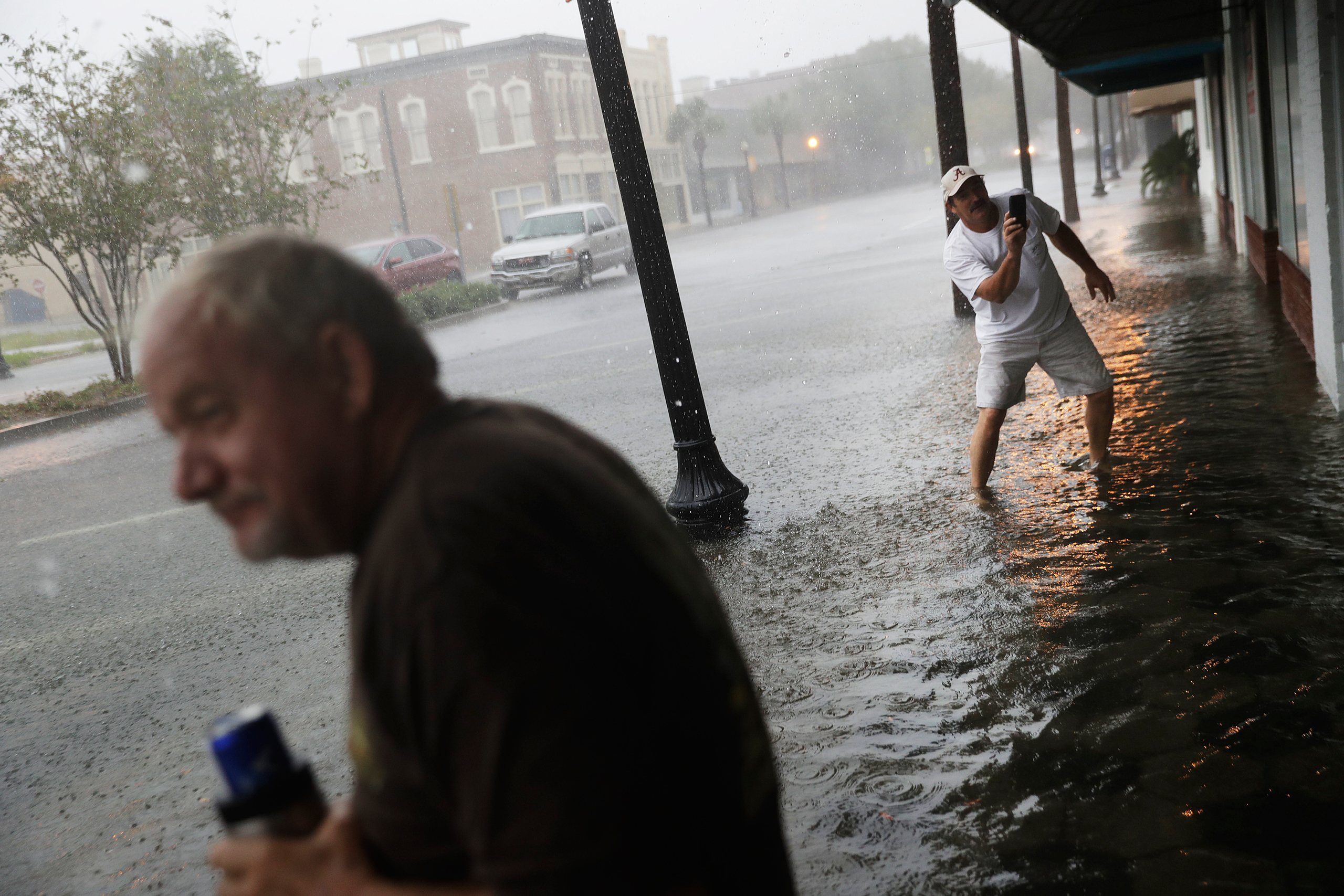 Keith Paseur, right, and Pat Barlow survey a flooded street from Hurricane Matthew as they check on a neighbor riding out the storm in their store in downtown Brunswick, Ga., on Oct. 7, 2016.