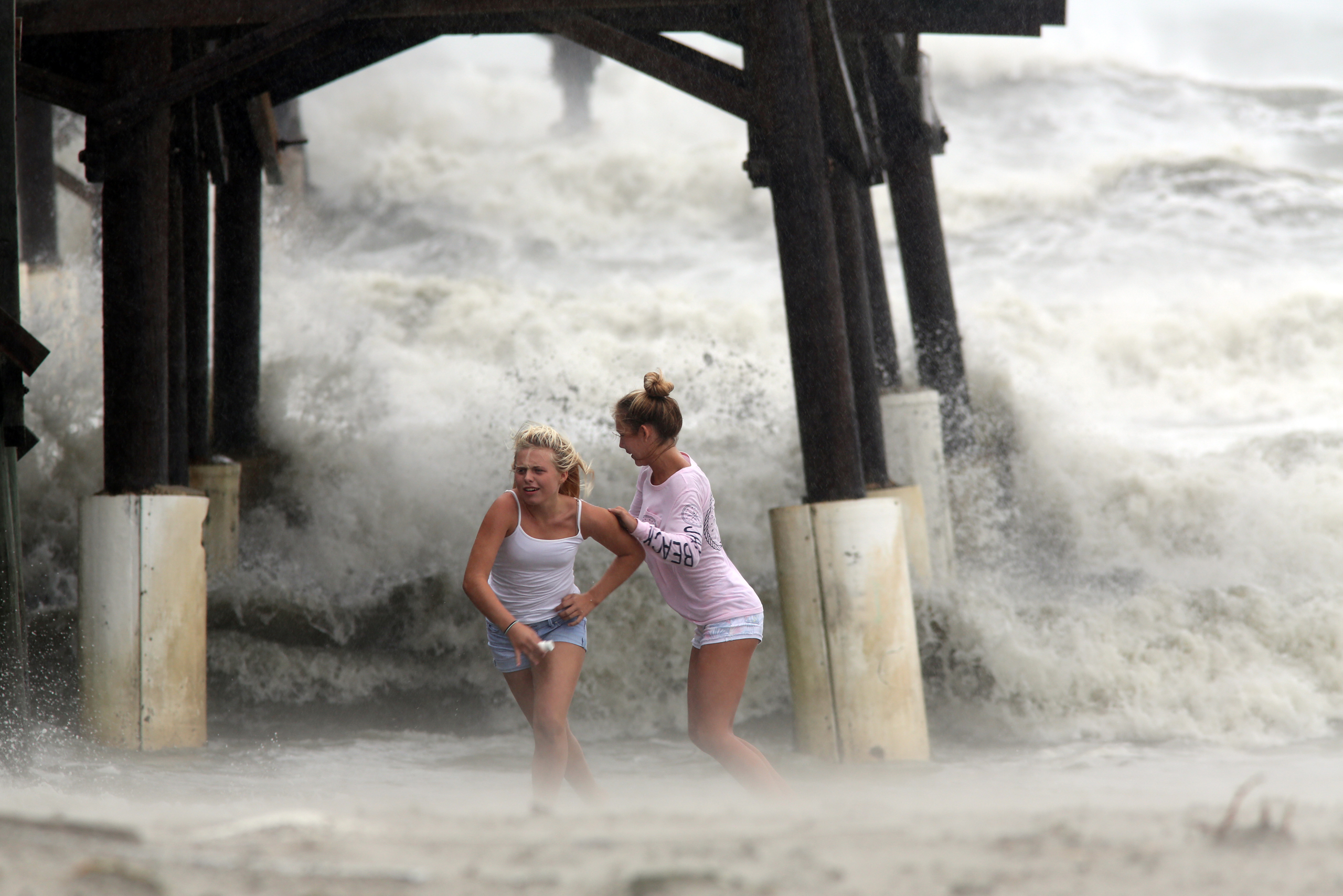 Kaleigh Black, 14, left, and Amber Olsen, 12, run for cover as a squall with rain and wind from the remnants of Hurricane Matthew pelt them as they explore the Cocoa Beach Pier in Cocoa Beach, Fla., on Oct. 7, 2016.