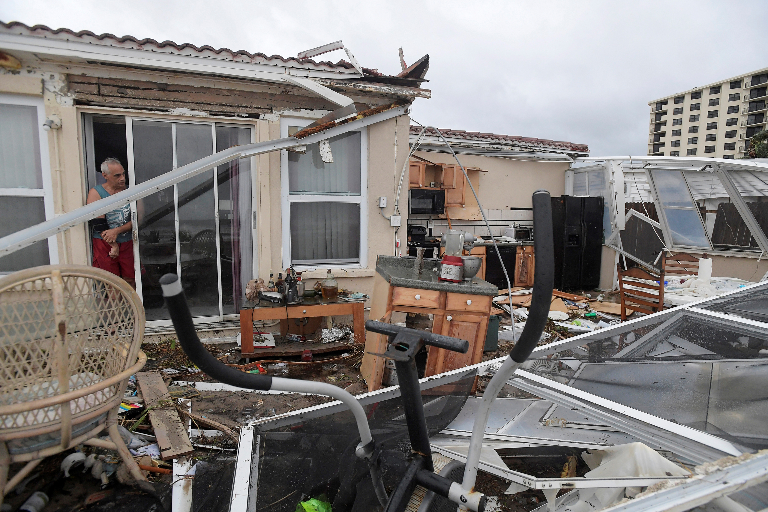 Joe Lovece surveys the damage to the kitchen at the back of his oceanfront home after the eye of Hurricane Matthew passed Ormond Beach, Fla., on Oct. 7, 2016.