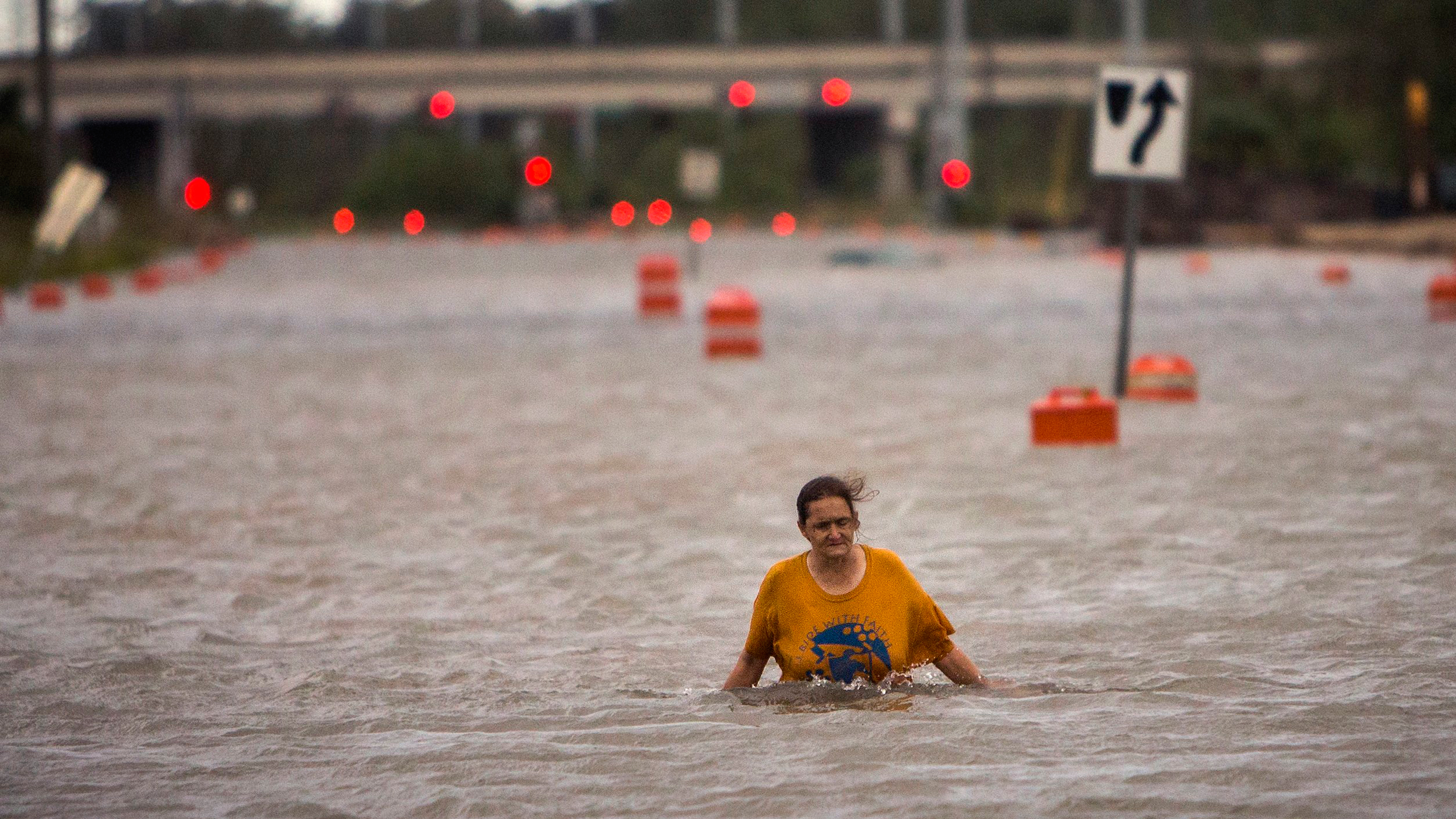 A woman who identified herself as Valerie walks along flooded President Street after leaving her homeless camp after Hurricane Matthew caused flooding in Savannah, Ga., on Oct. 8, 2016.