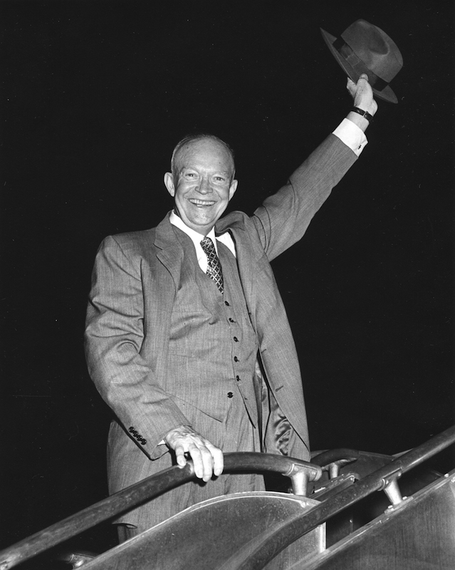 US President Dwight Eisenhower (1890 - 1965) smiles broadly and waves his hat as be boards a plane, July 20, 1956.