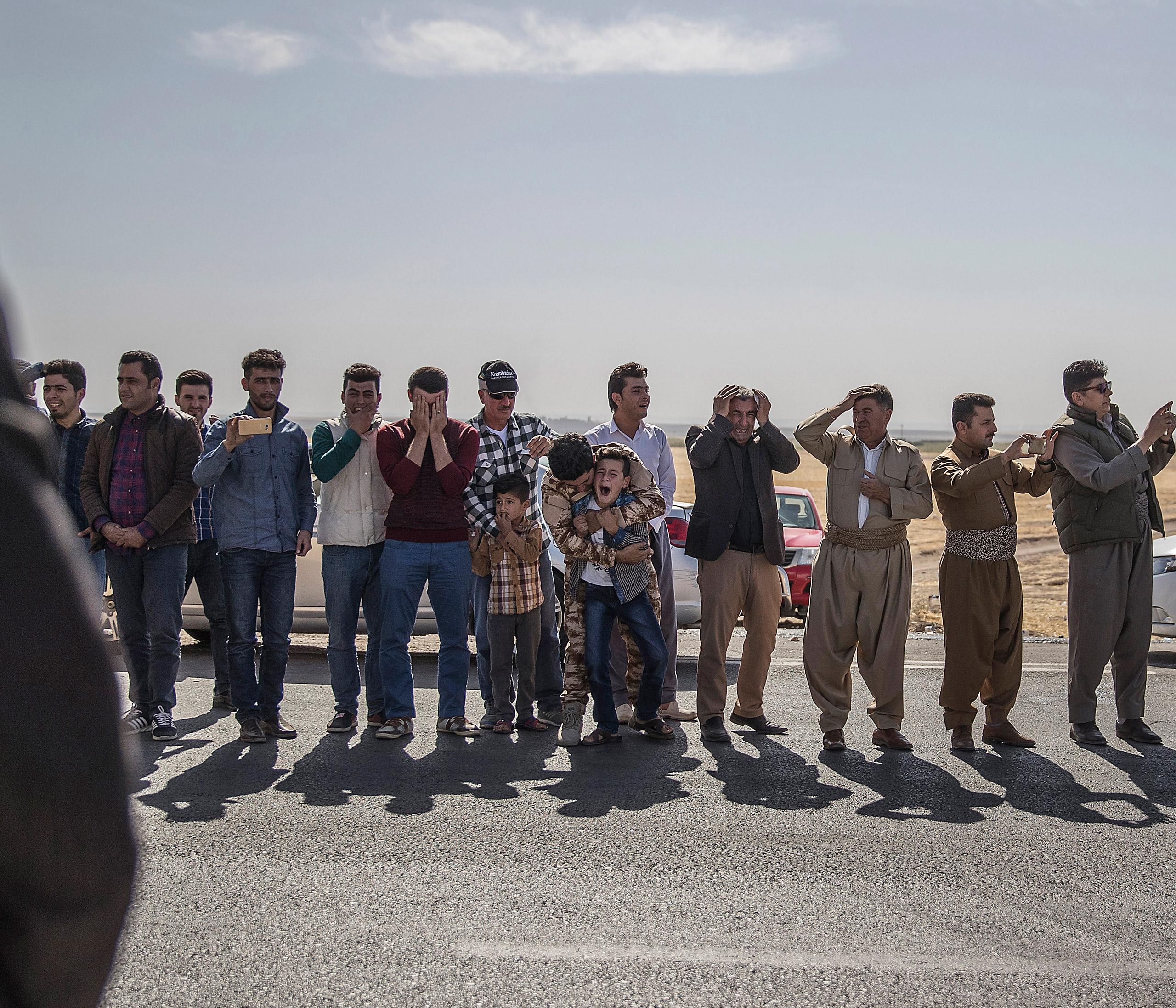 Thousands of people gather at the funeral of five Peshmerga soldiers killed by an IED explosion. One of the dead soldier's sons, Lefaws, 11, breaks down and screams when the ambulance passes by  with an image of his father mounted on the front of the car. Behind him, his brother, Shalews, silently cries. Khalifa, Iraq, Oct. 2016.