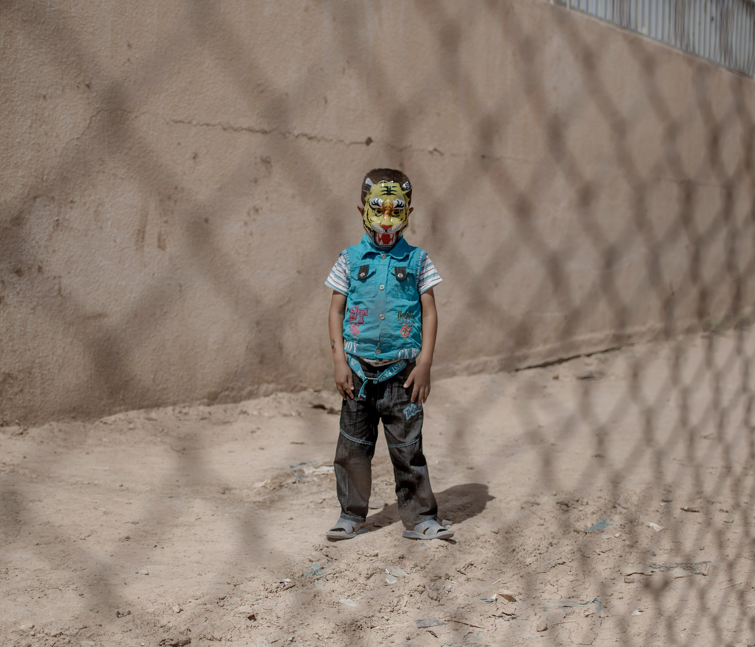 A young boy poses for a portrait at the Debaga refugee camp, an old football stadium that's been turned into a temporary home for thousands of refugees fleeing the war between ISIS and coalition troops in northern Iraq, Oct. 2016.