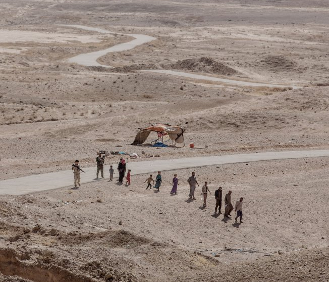 Eight children and four adults escaped their ISIS controlled village outside Mosul. After walking through the desert for three days, they reached Kurdish Peshmerga troops who searched them for weapons before transporting them to a refugee camp. Kurdistan, Iraq, Sept. 2016