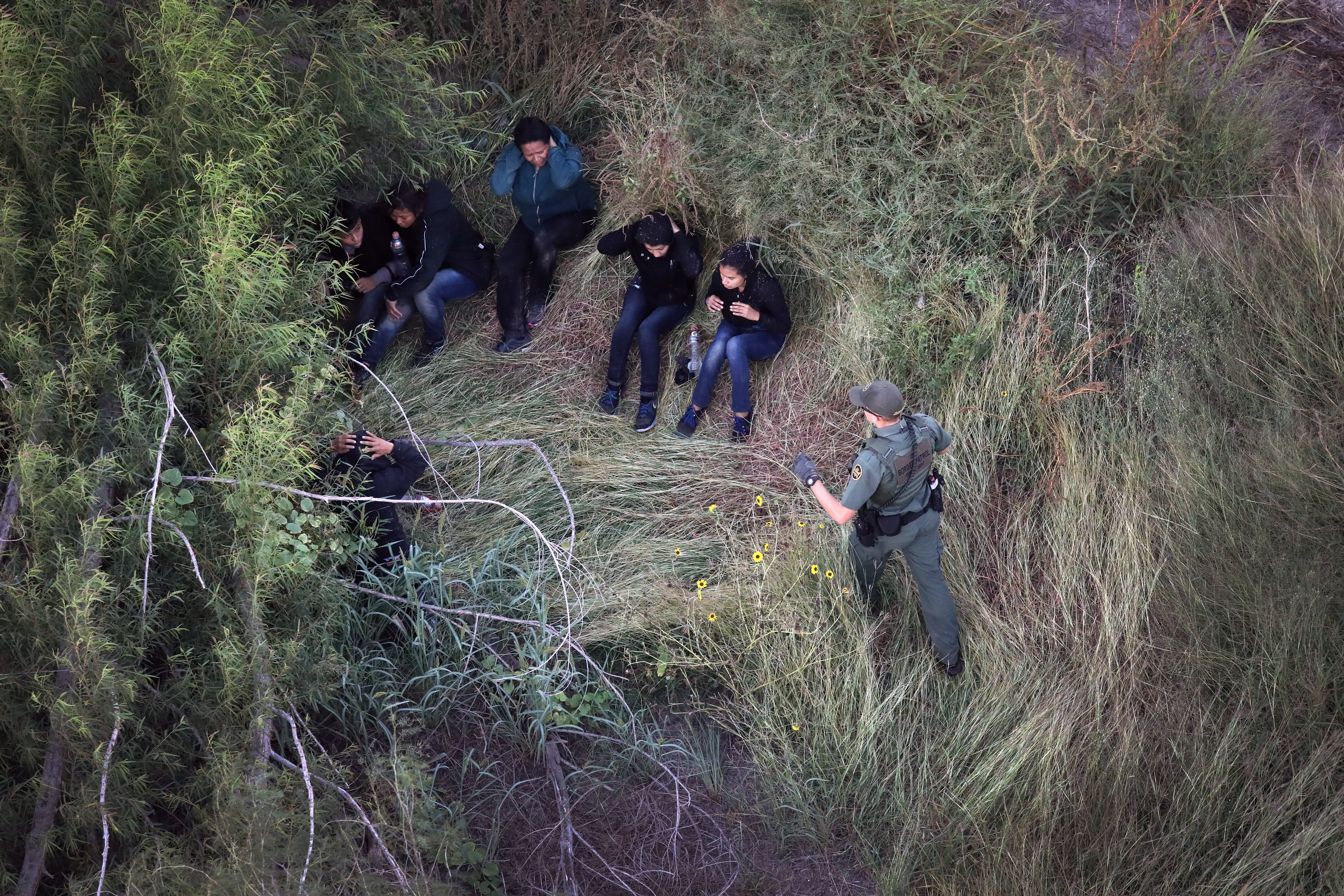 A U.S. Border Patrol agent detains a group of undocumented immigrants on Oct. 18, 2016 near McAllen, Texas.