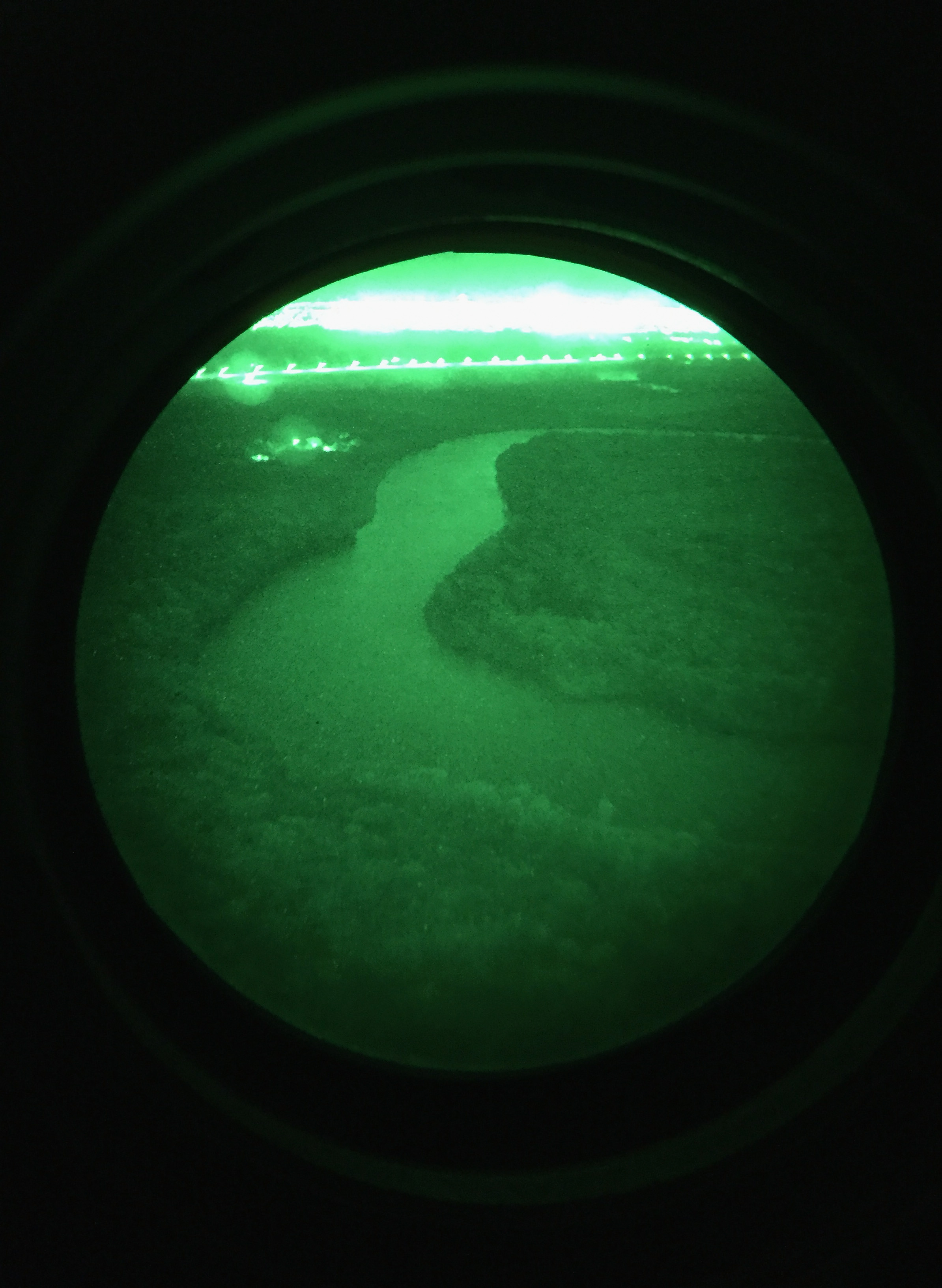 This photo made with a smart phone through night vision goggles shows the Rio Grande flowing along the U.S.-Mexico border, as seen from a U.S. Customs and Border Protection helicopter during a patrol over the U.S.-Mexico border on Oct. 18, 2016 in McAllen, Texas.