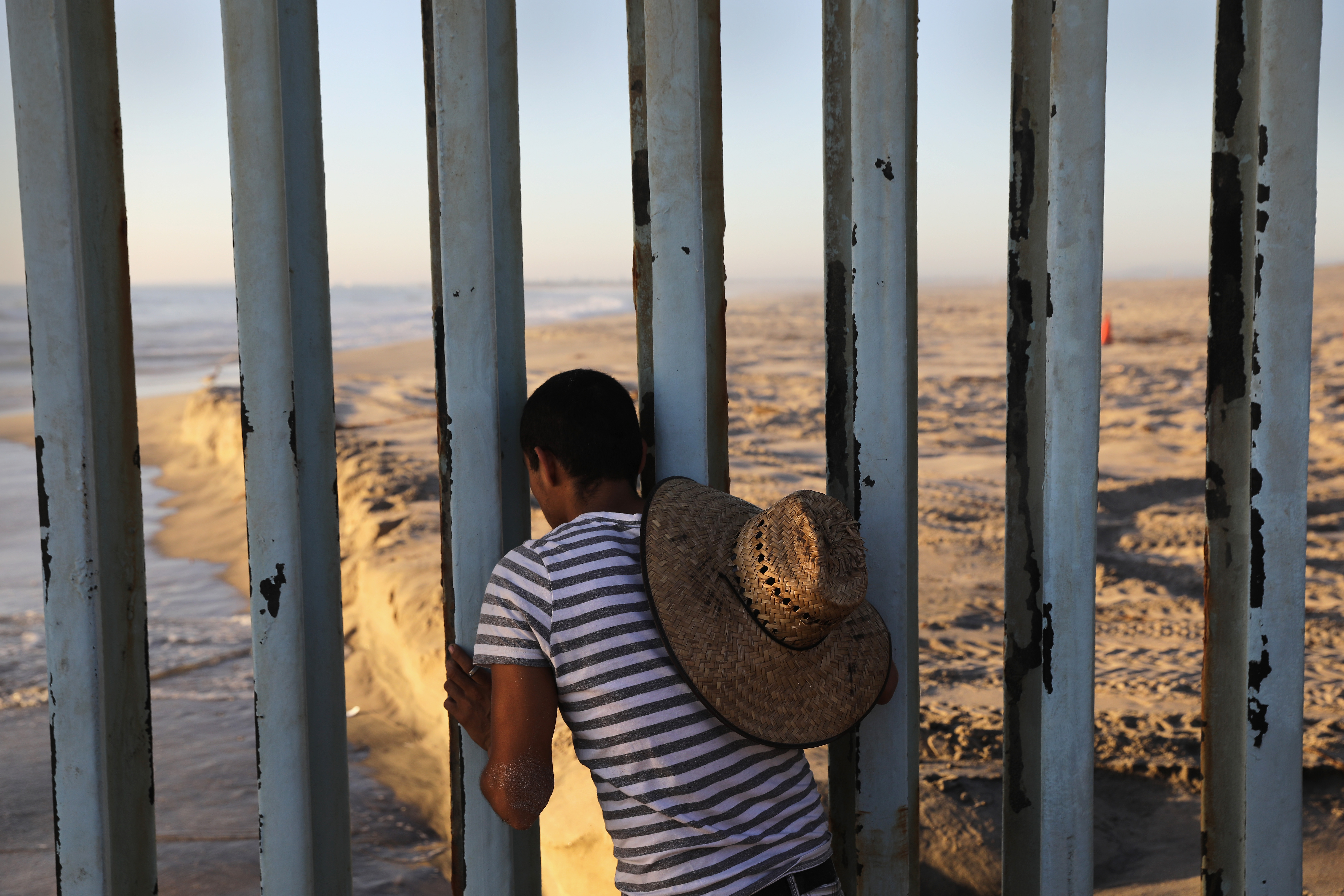 A man looks through the U.S.-Mexico border fence into the United States on Septt. 25, 2016 in Tijuana, Mexico.