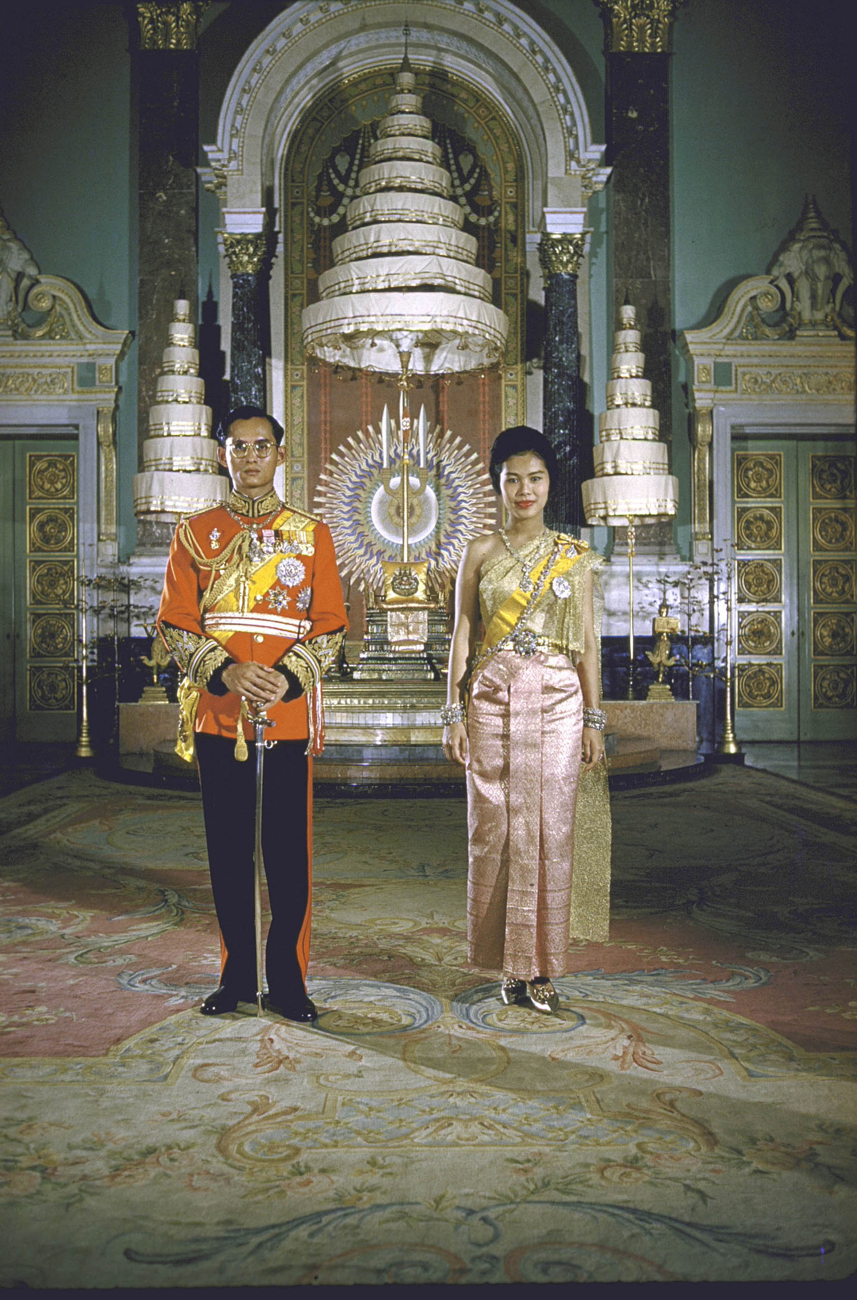 Formal portrait of King Bhumibol Adulyadej  and Queen Sirikit at the Palace in 1960. The nine-tiered parasol in the background is a symbol of the Chakri Dynasty.