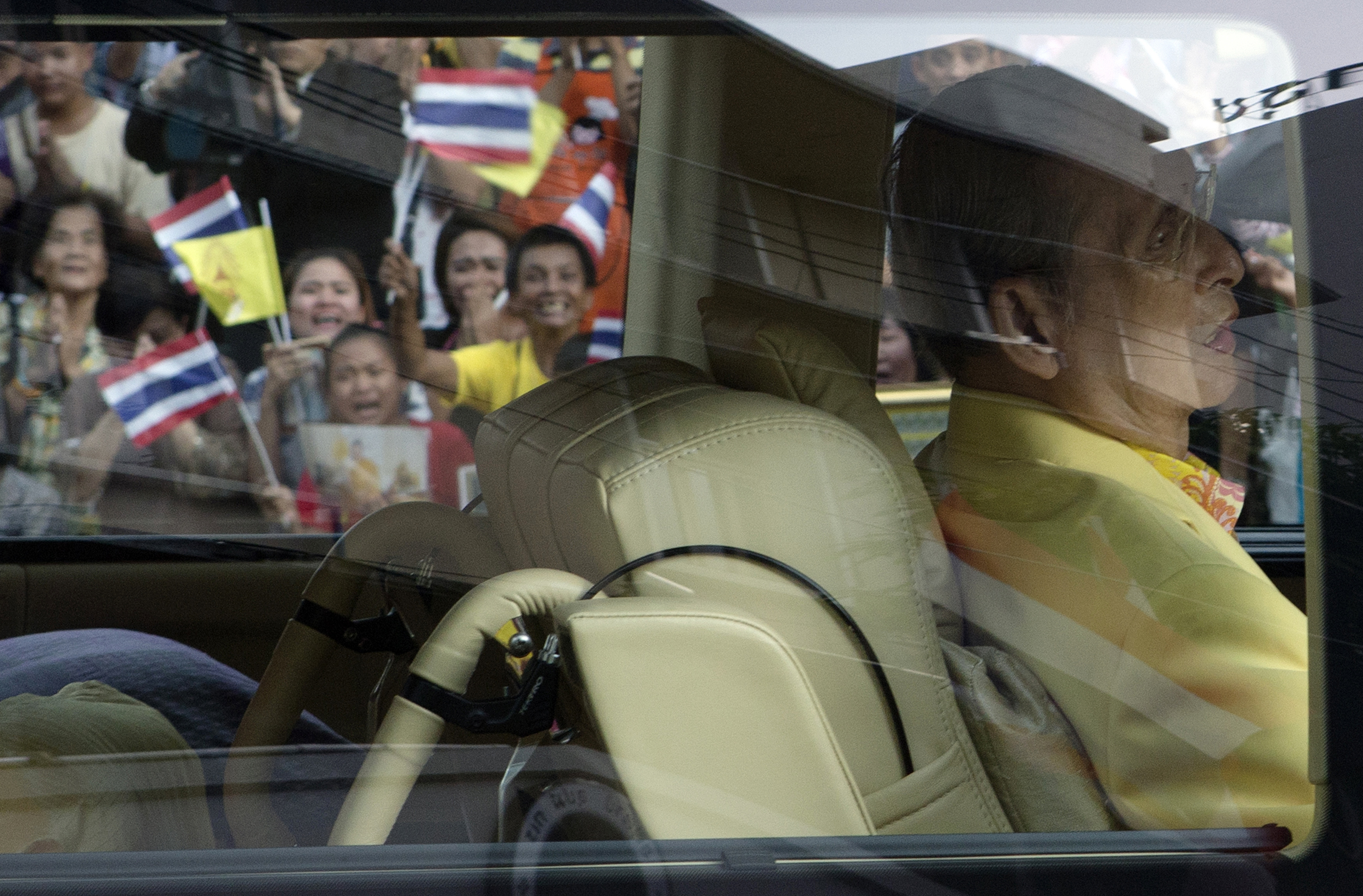 Well-wishers wave flags and pray as King Bhumibol Adulyadej leaves Siriraj hospital in Bangkok on Sept. 15, 2014.