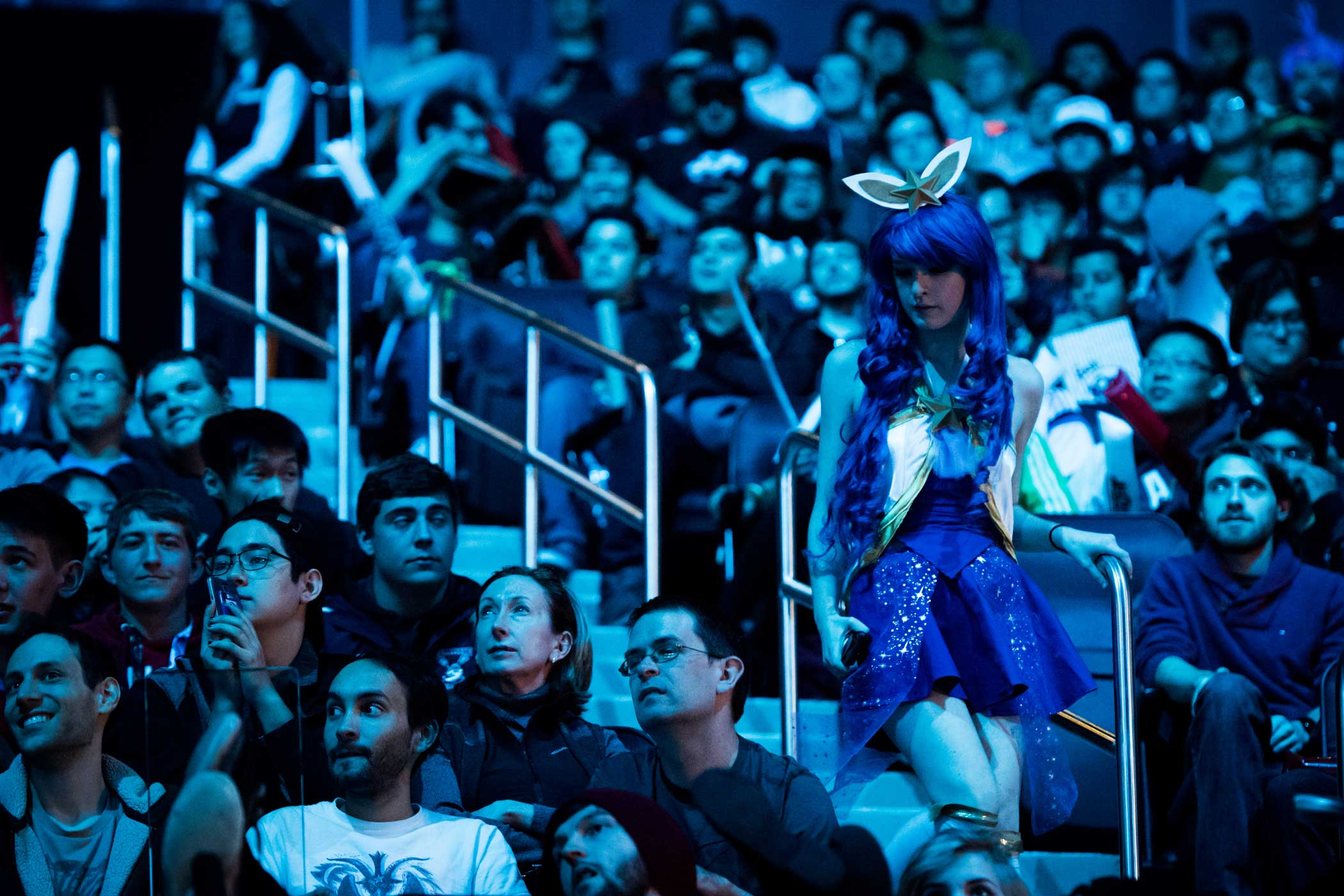 A League of Legends fan wearing a cosplay outfit heads to her seat.