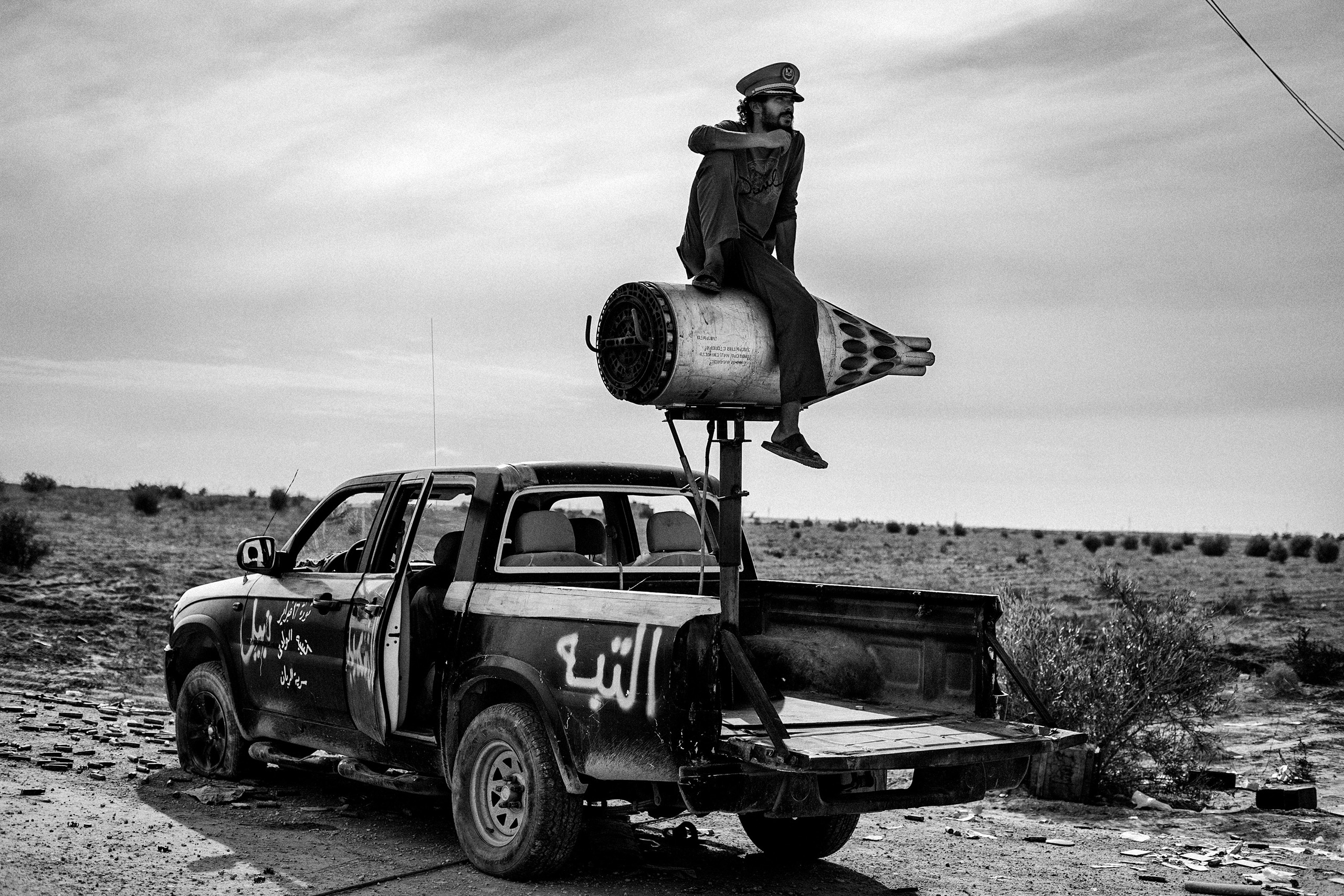 A revolutionary soldier sits atop a rocket mounted on a pickup in the desert near Sirte, Libya, Oct. 6, 2011.