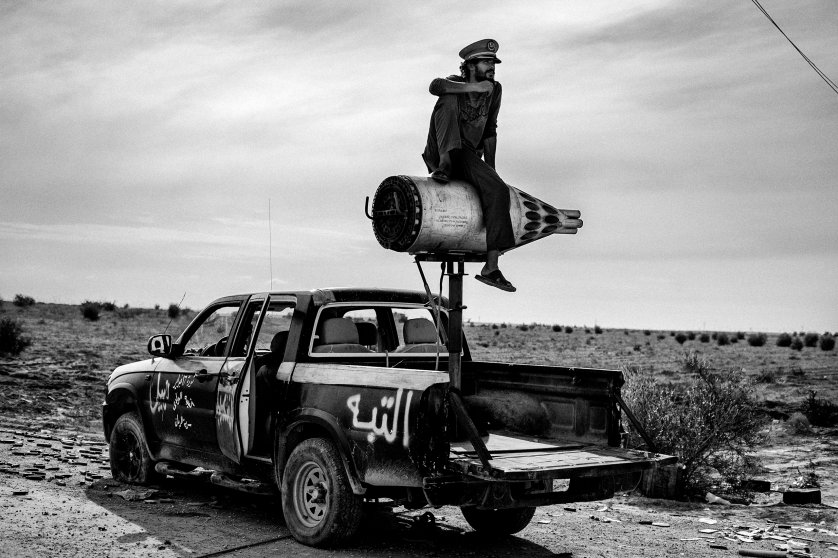 A revolutionary soldier sits on a rocket mounted on a pickup in the desert near Sirte on Oct. 6, 2011.