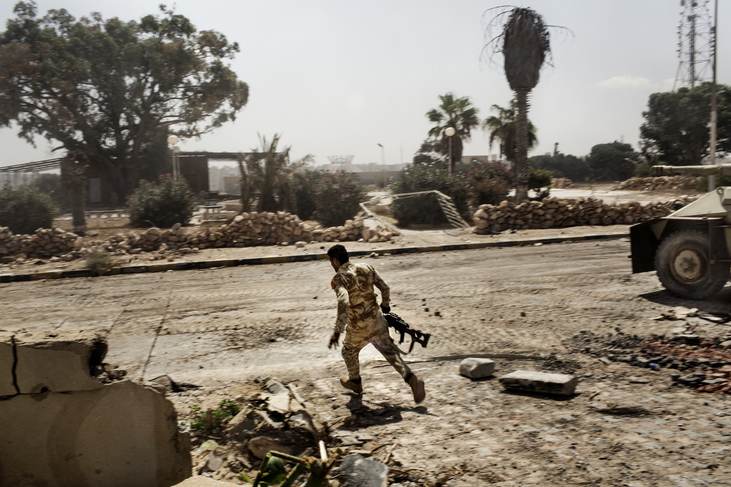 A Libyan fighter affiliated with forces of the Tripoli government runs for cover while fighting against Islamic State positions in Sirte, Libya, Sept. 22, 2016.