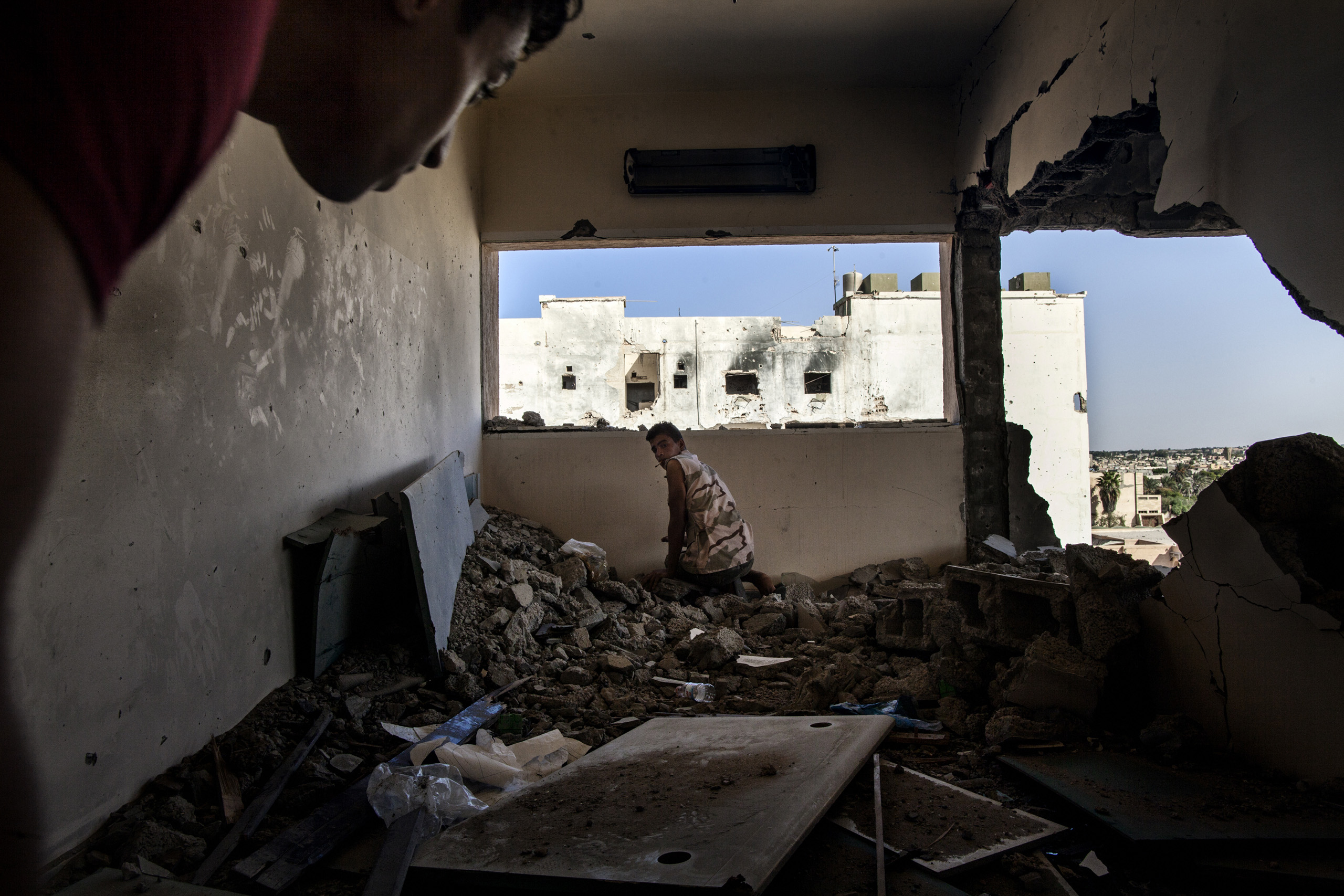 Fighters of the Libyan forces affiliated with the Tripoli government try to spot ISIS positions from a destroyed building close to the frontline in District 3, Sirte, the last Libyan stronghold of Islamic State militants, Sept. 23, 2016.