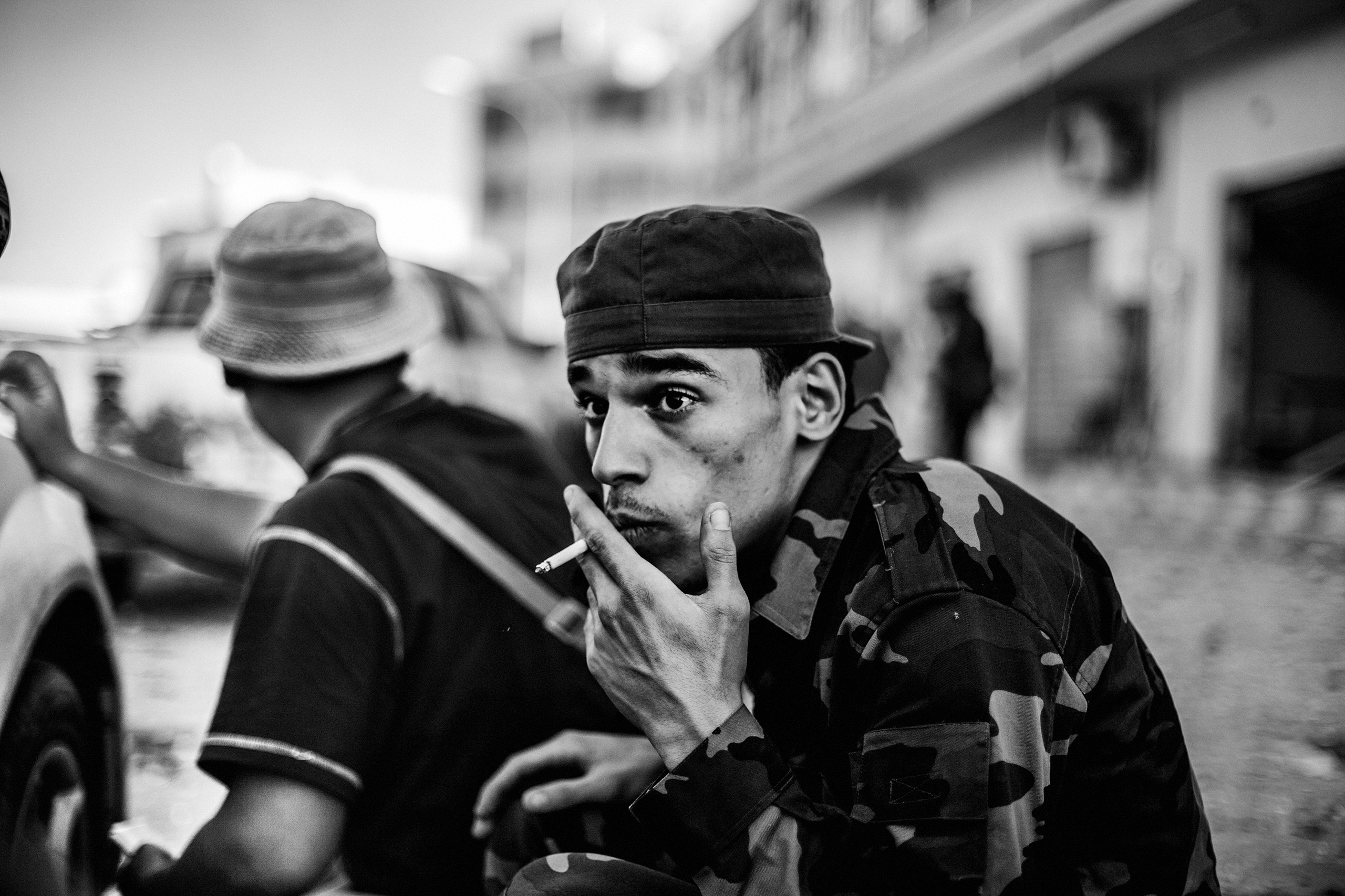 A revolutionary fighter seeks shelter from sniper fire by forces loyal to Muammar Gaddafi, Sirte, Libya,  Oct. 12, 2011.