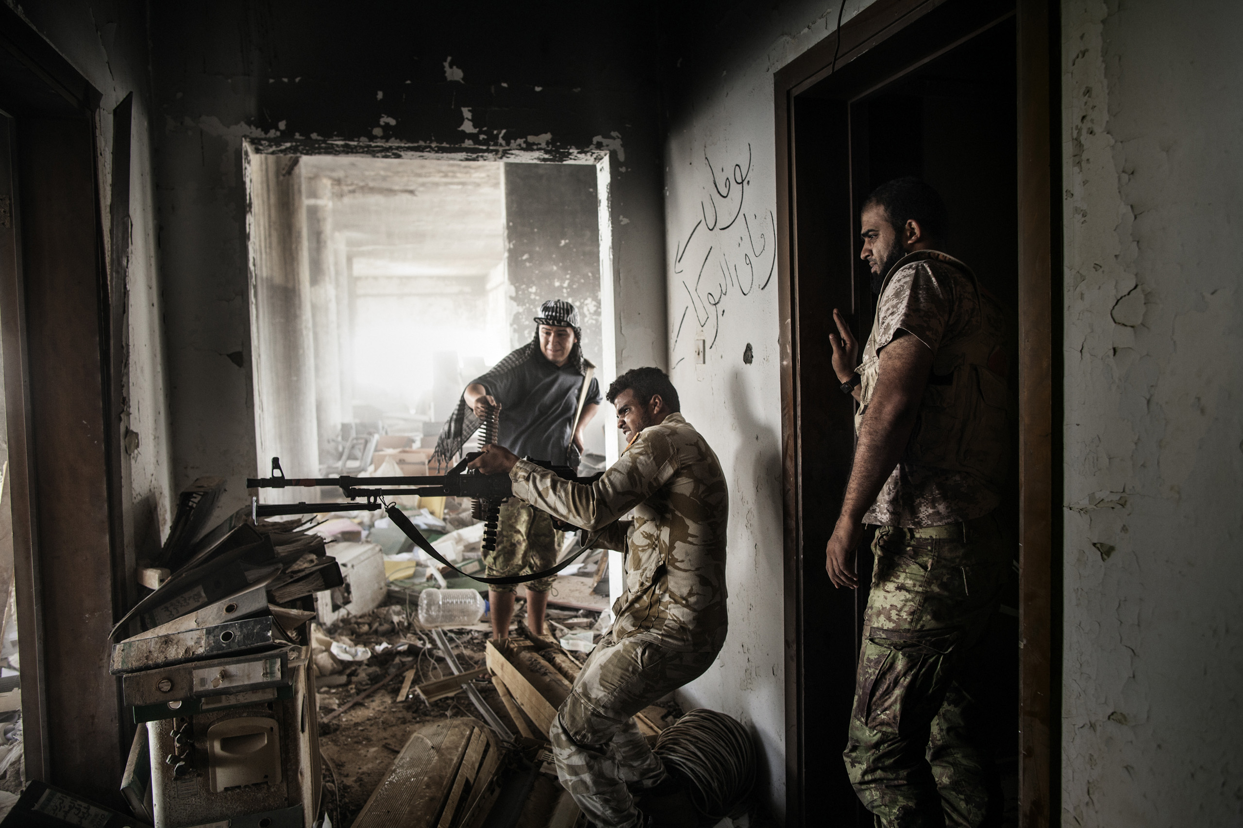 A Libyan fighter affiliated with the Tripoli government fires his weapon towards ISIS positions in Sirte, Libya, Sept. 22, 2016.