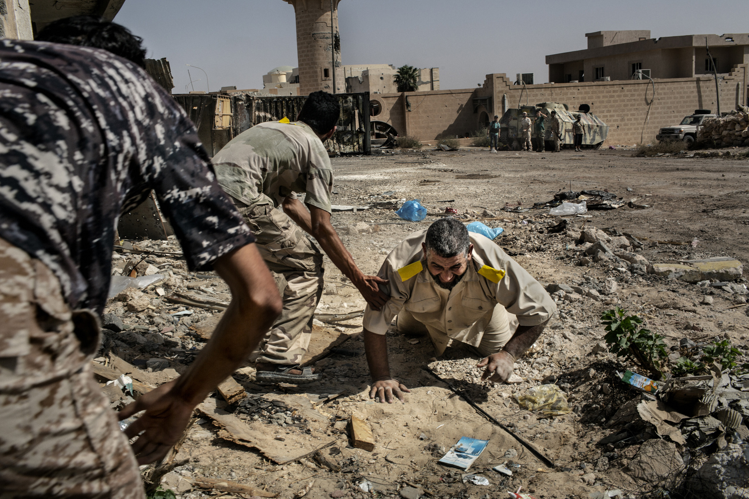 A fighter loyal to Libya's Government of National Accord is helped by two  comrades after he was shot in the leg by an ISIS (Islamic State) sniper on the western frontline, Sirte, Oct. 2, 2016.