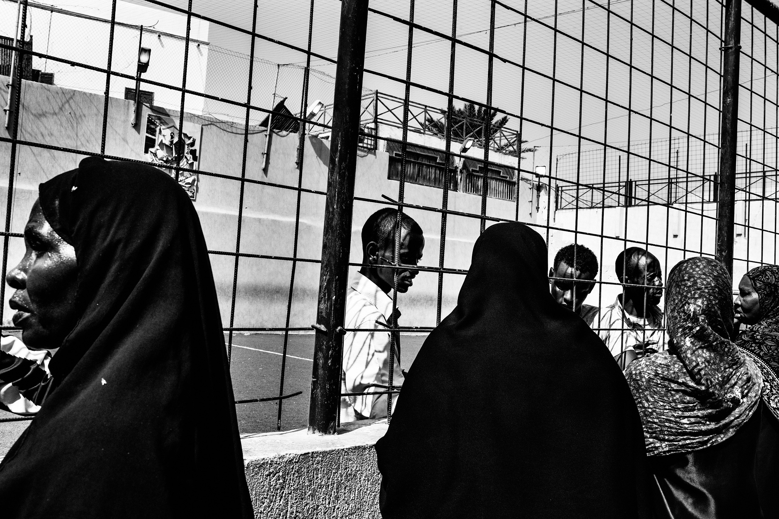 Women talk with their husbands, suspected to be Gaddafi's mercenaries, imprisoned in a football field converted into a prison in Tripoli on Sept. 2, 2011.