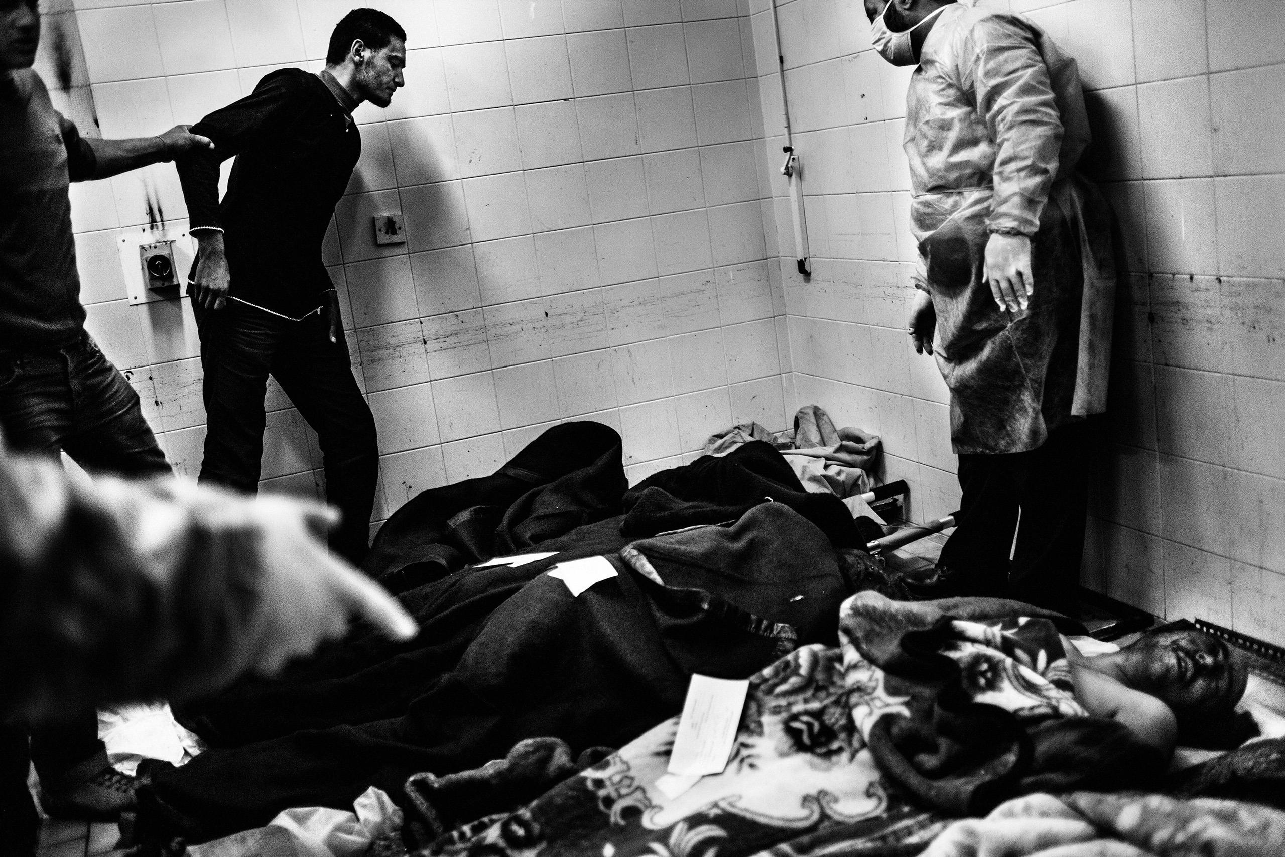 The relative of a victim approaches the body of a revolutionary fighter to make an identification. The victims were killed during the fighting against Gaddafi's forces on March 4, 2011, in  Benghazi, Libya.