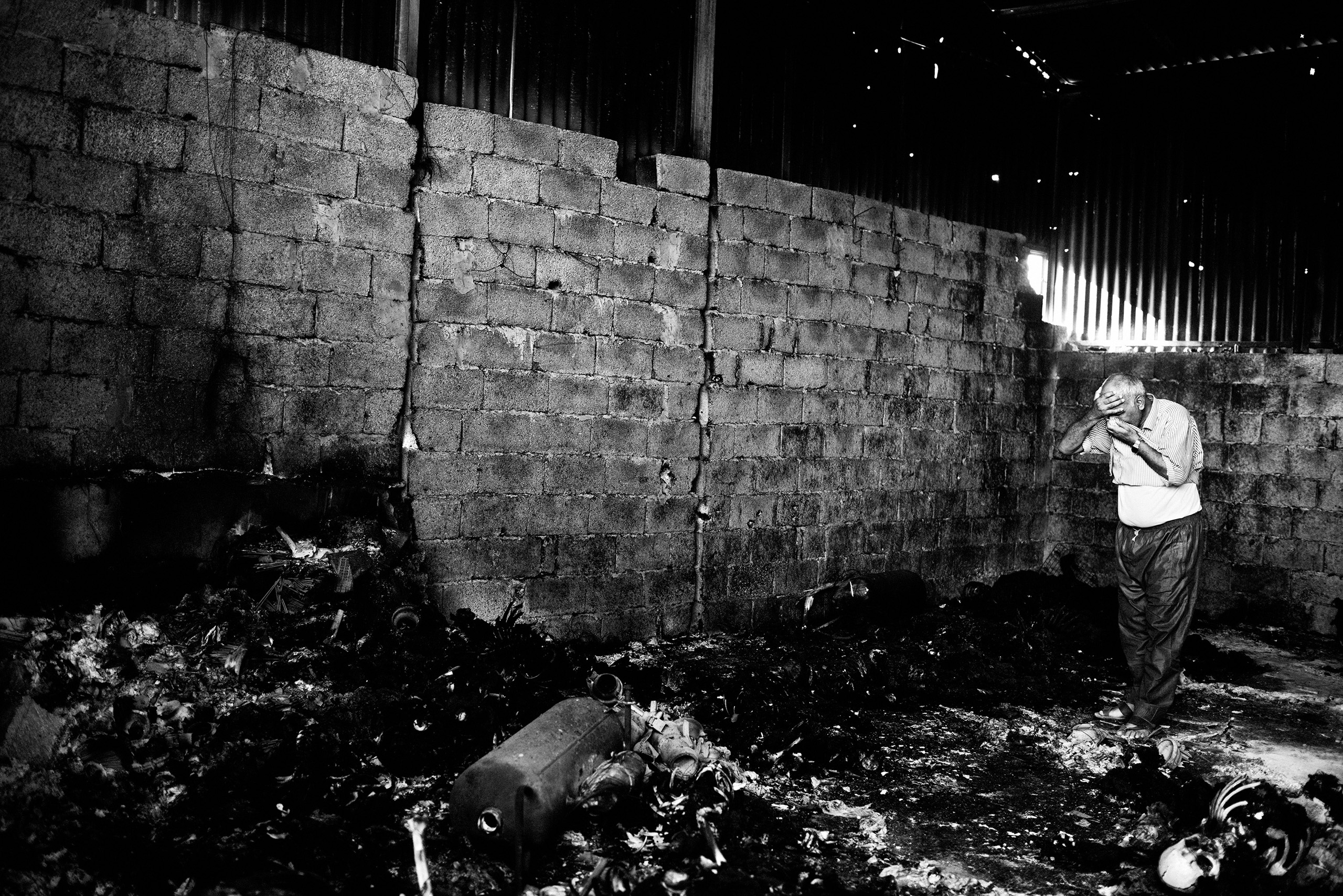 A Libyan man inside the warehouse that holds the remains of 50 burned bodies. Suburbs of Tripoli, Libya. Aug. 27, 2011.