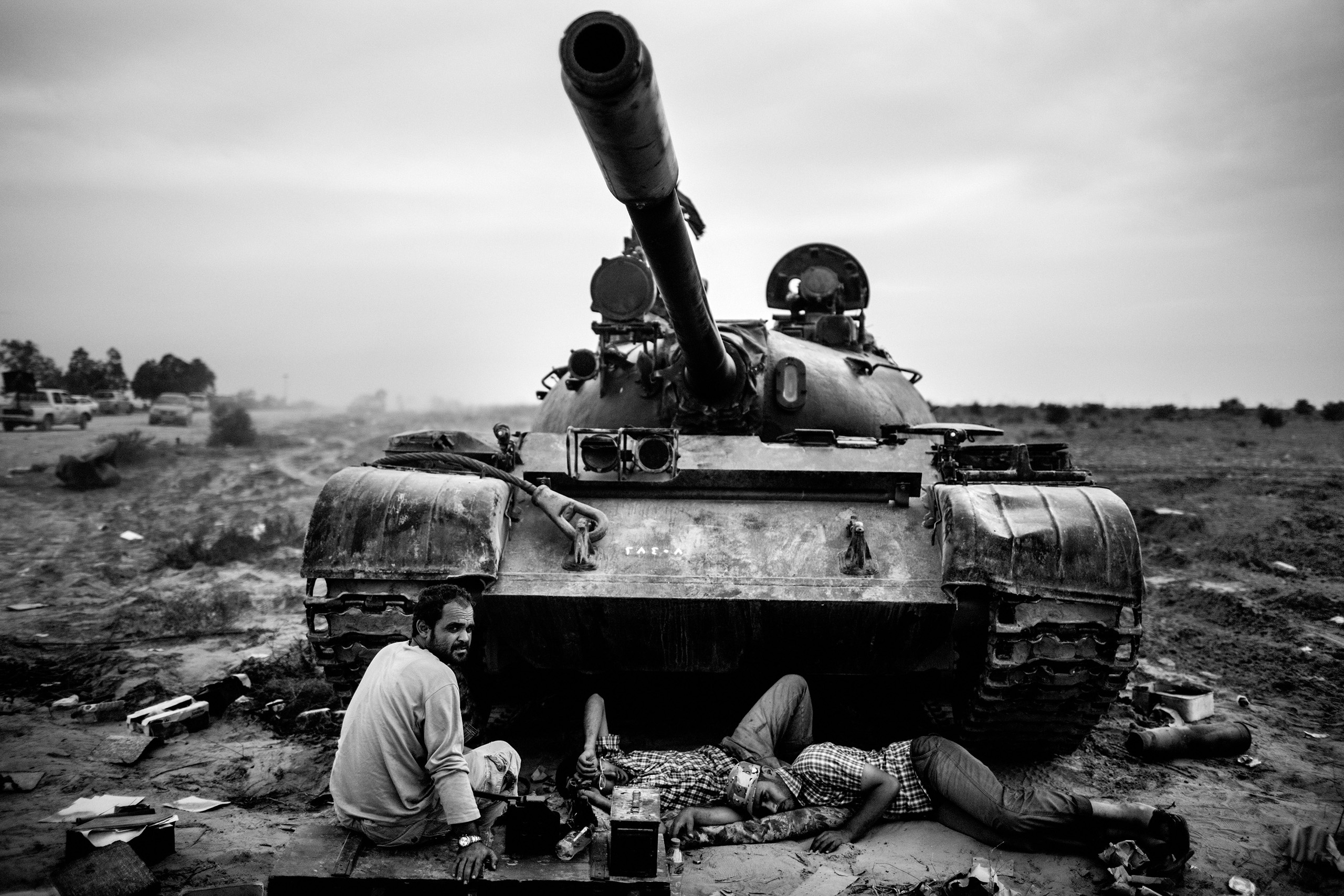 Revolutionary fighters  rest near a tank during fighting for control of the Libyan city of Sirte, Oct. 7, 2011.