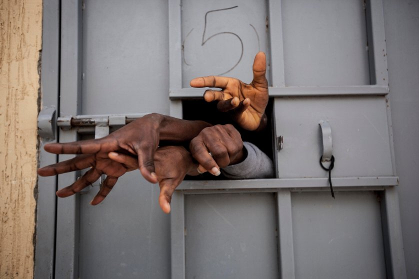 Sub-Saharan migrants and refugees reach through the window of a cell in a detention center in Garabuli, Libya, pleading for water, cigarettes, food and their release.