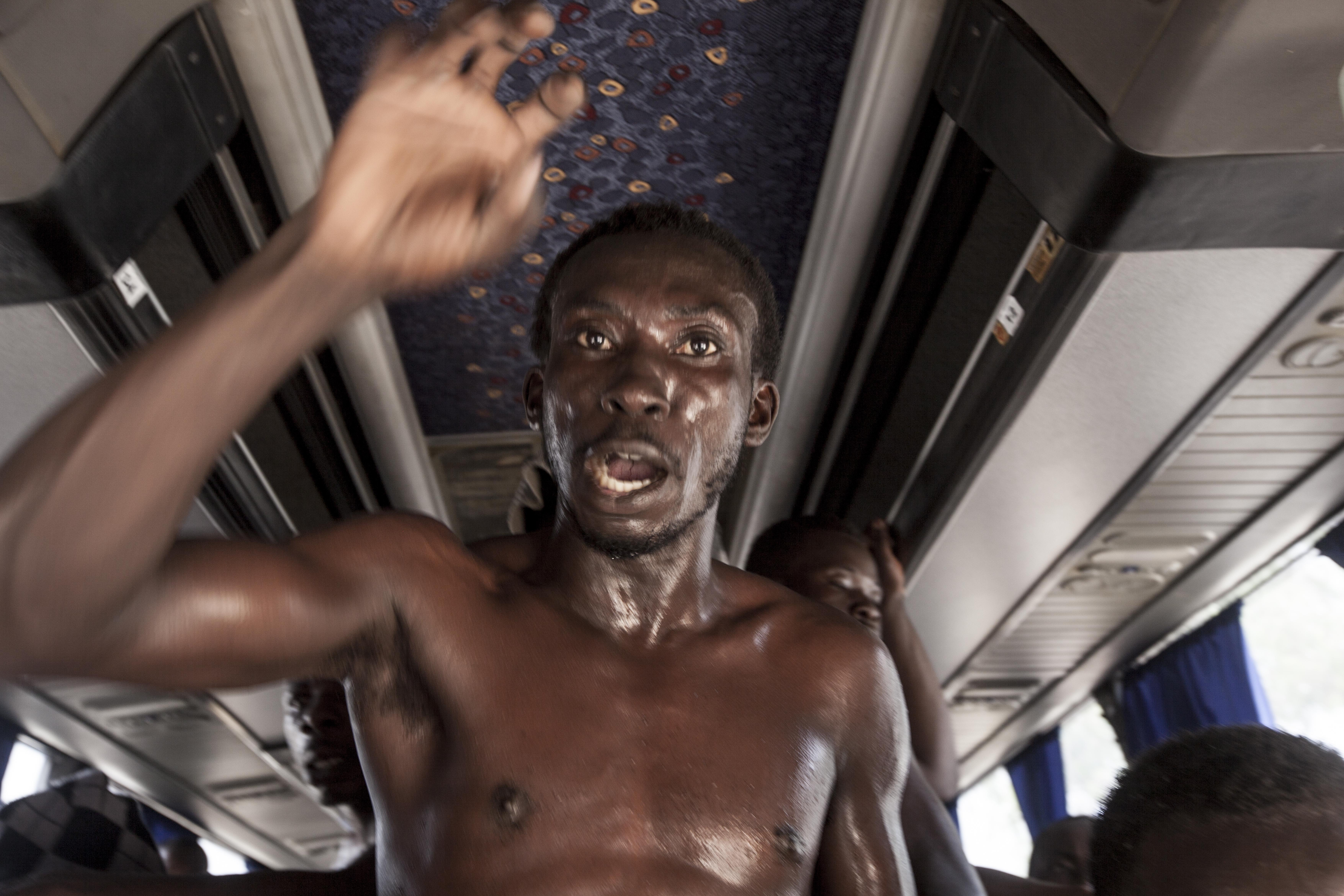 A Sub-Saharan migrant complains as he waits to be transferred from a detention center in Surman, after he was sold by a militia group in the northwest of Libya.