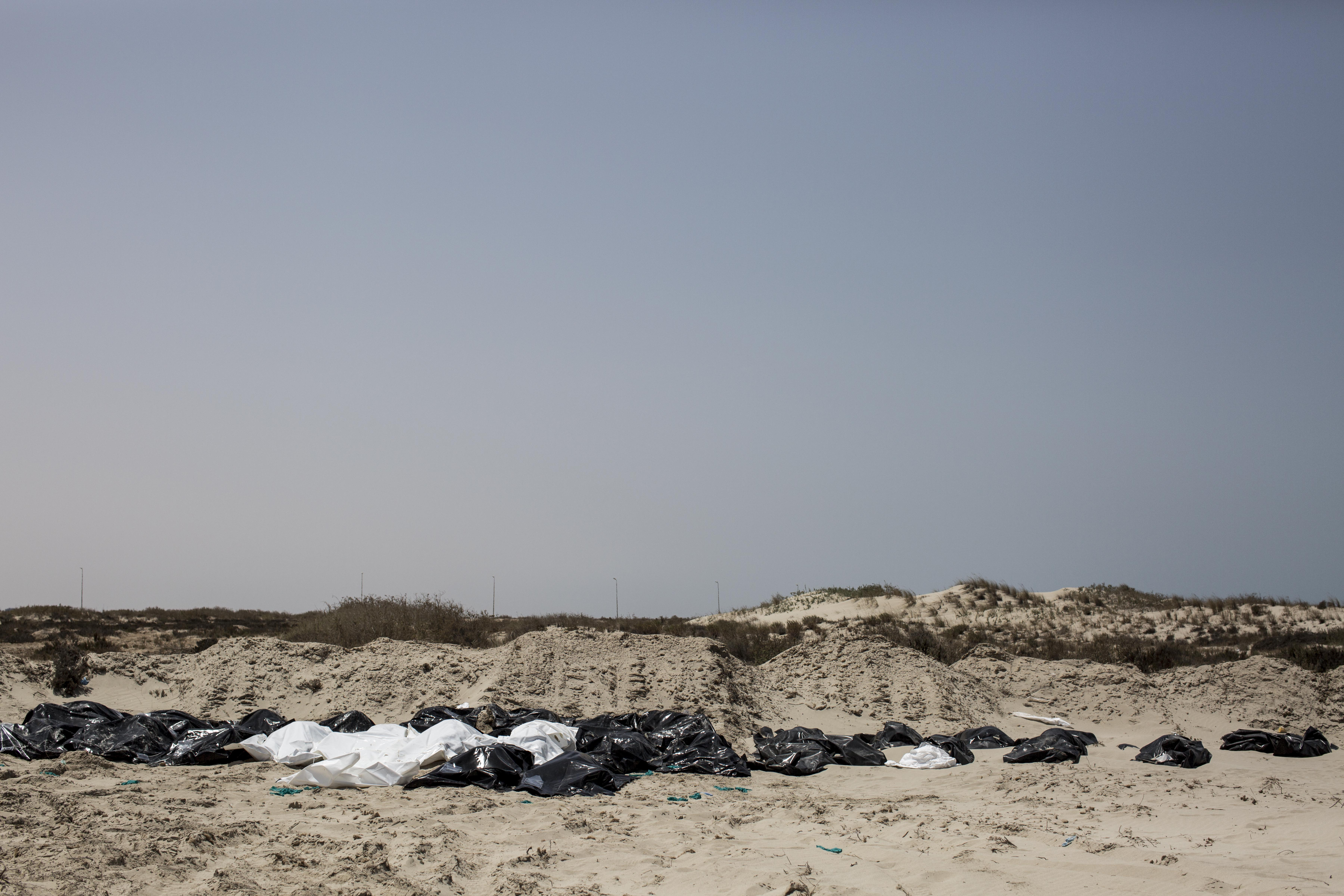 The bodies of dead migrants are lined up for burial at an improvised graveyard in Abu Kammash, Libya.
