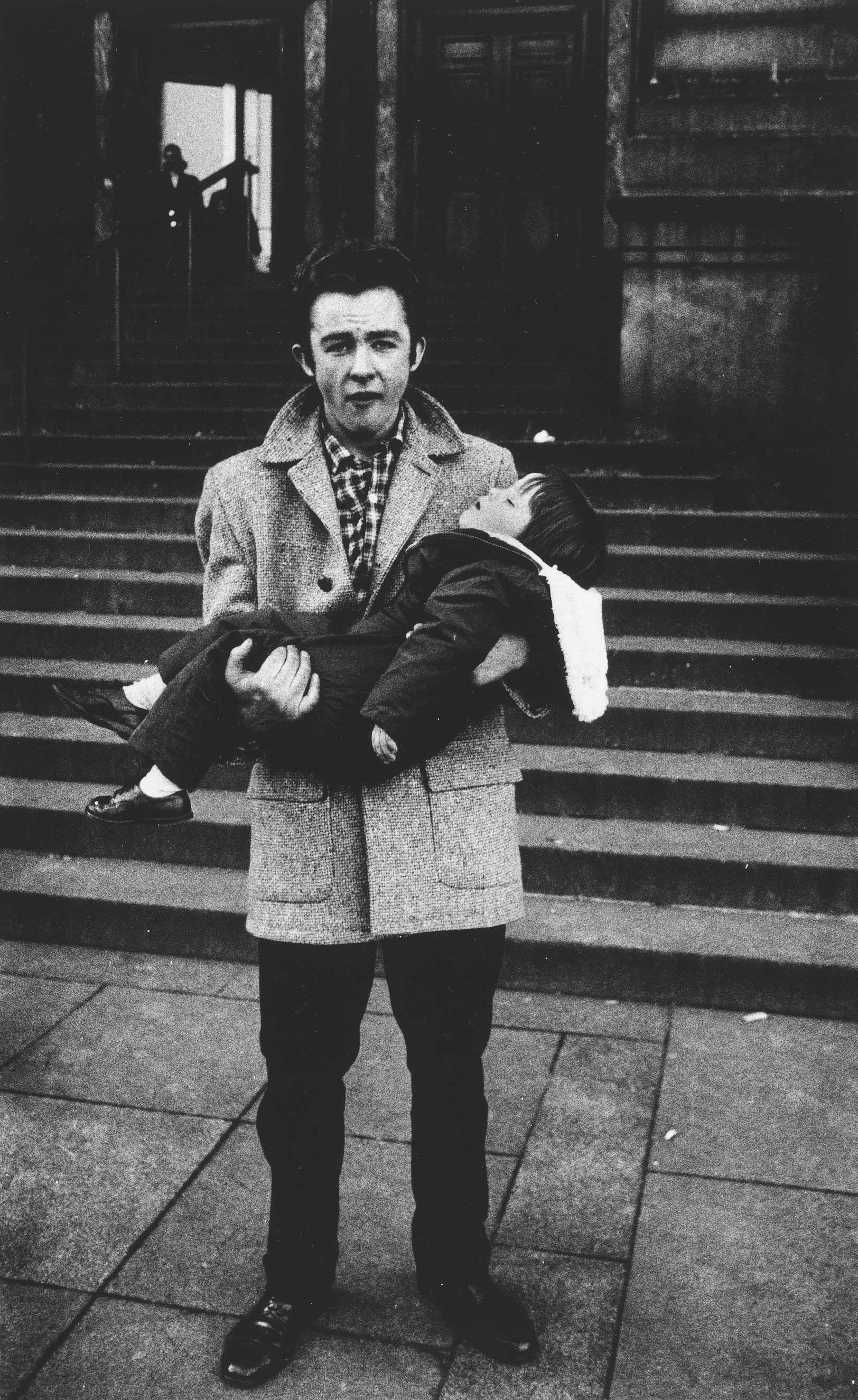 Man holding a sleeping child, N.Y.C, 1957                               Yola Monakhov Stockton: Arbus' biography as mother and photographer of the complex theater of human affections comes to mind when looking at her photographs depicting men (instead of fathers) holding their children. This scenario could be an obverse self-portrait – a child in place of camera, the father addressing the camera's gaze. Behind the figures, granite steps leading toward (instead of to) heavy doorways suggest a public building and institutional rites of passage. The father's emotive face, turned-up collar, shiny shoes and raffish coiffure channel James Dean, but here his hands strain to hold a sleeping boy who is wearing the same proper shoes in miniature. A new Madonna and child, of fatherhood and aspiration on a New York City street, is recognized as uncertain ceremony, a weight to feel.