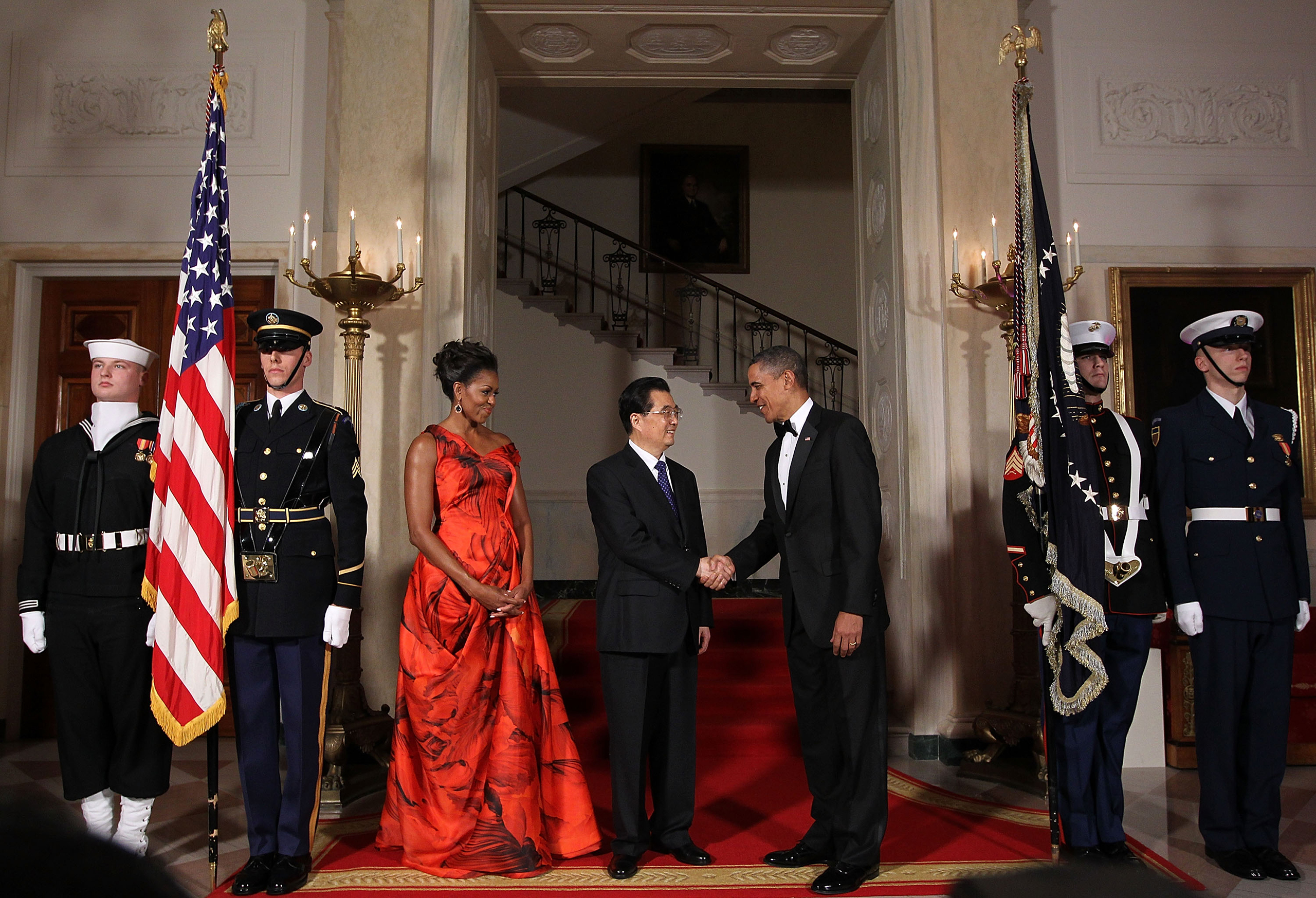 Barack Obama (R) shakes hands with Chinese President Hu Jintao (C) as Michelle Obama looks on as they pose for the official photo at the Grand Staircase of the White House in Washington, D.C., on Jan.19, 2011.