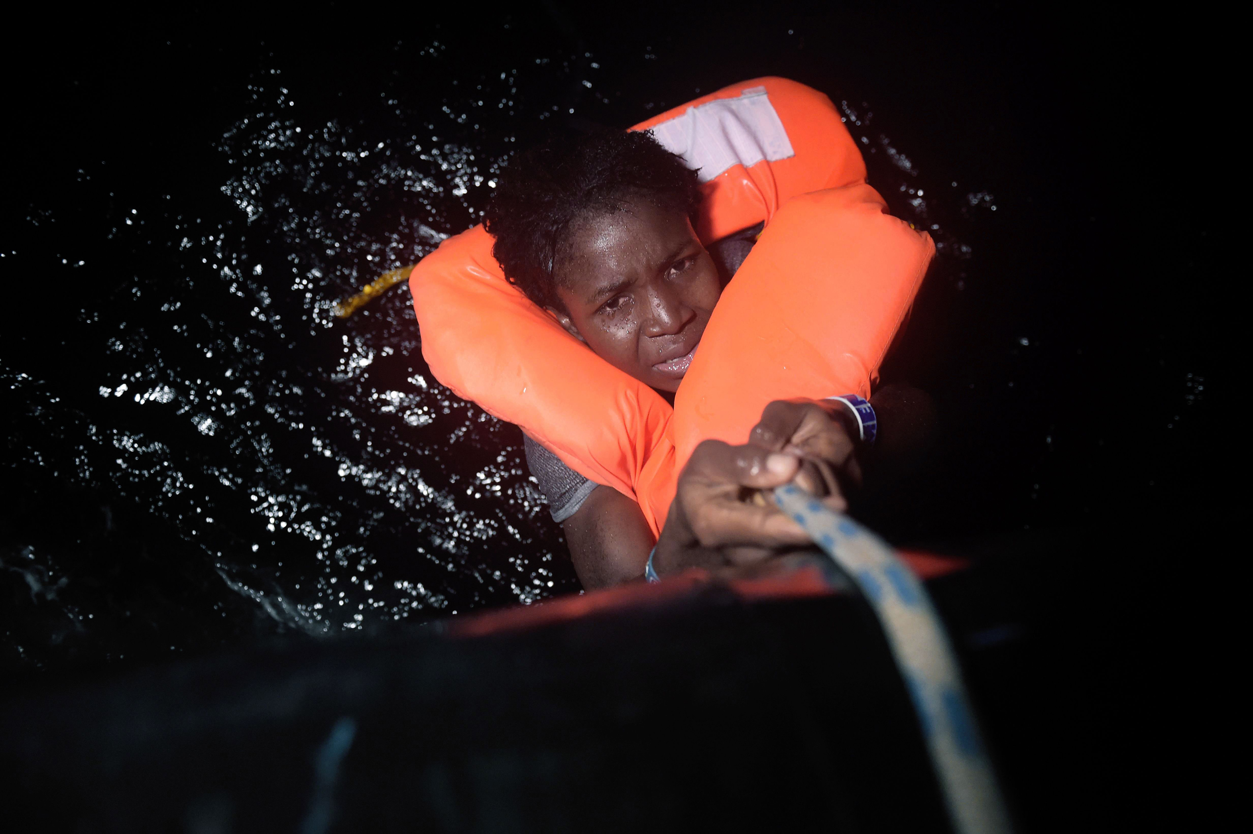 A migrant holds onto a rope during a rescue operation some eight nautical miles off Libya's Mediterranean coastline on Oct. 12, 2016.