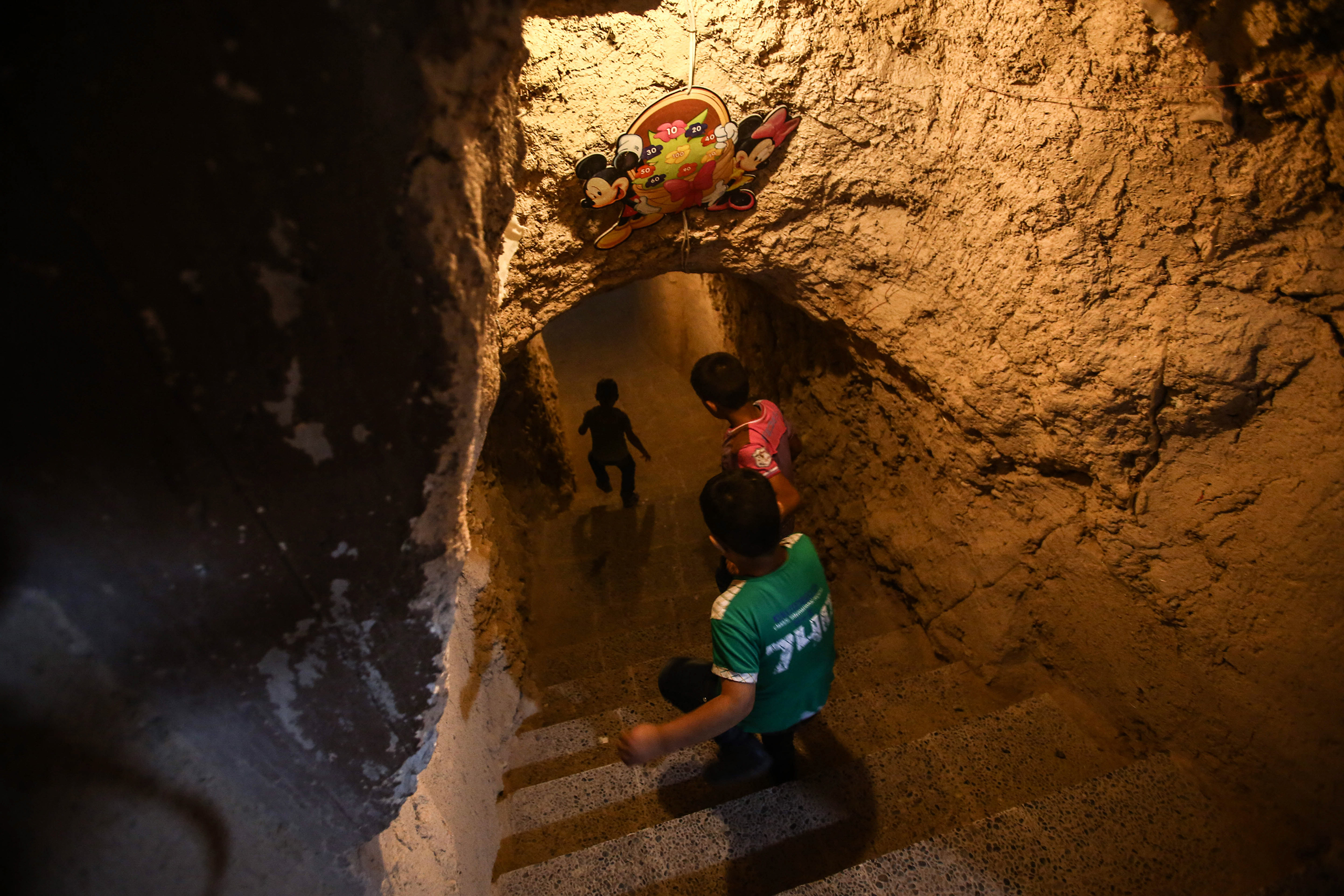 Children walk through a tunnel connecting the two halls of an underground amusement park in  Arbin, outside Damascus, Syria, on Sept. 16, 2016.