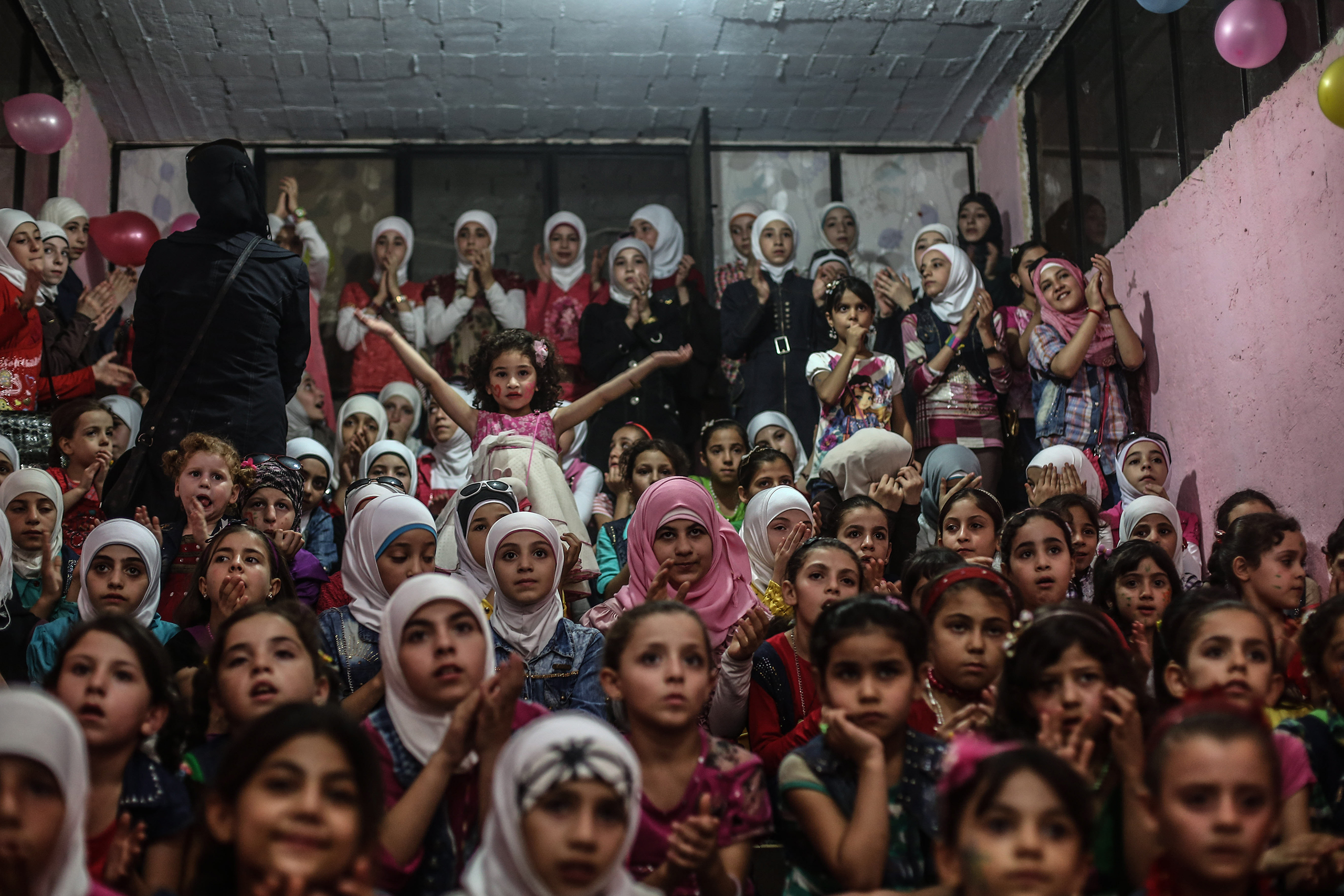 Children react as they listen to songs at an underground amusement park in  Arbin, outside Damascus, Syria, on Sept. 16, 2016.
