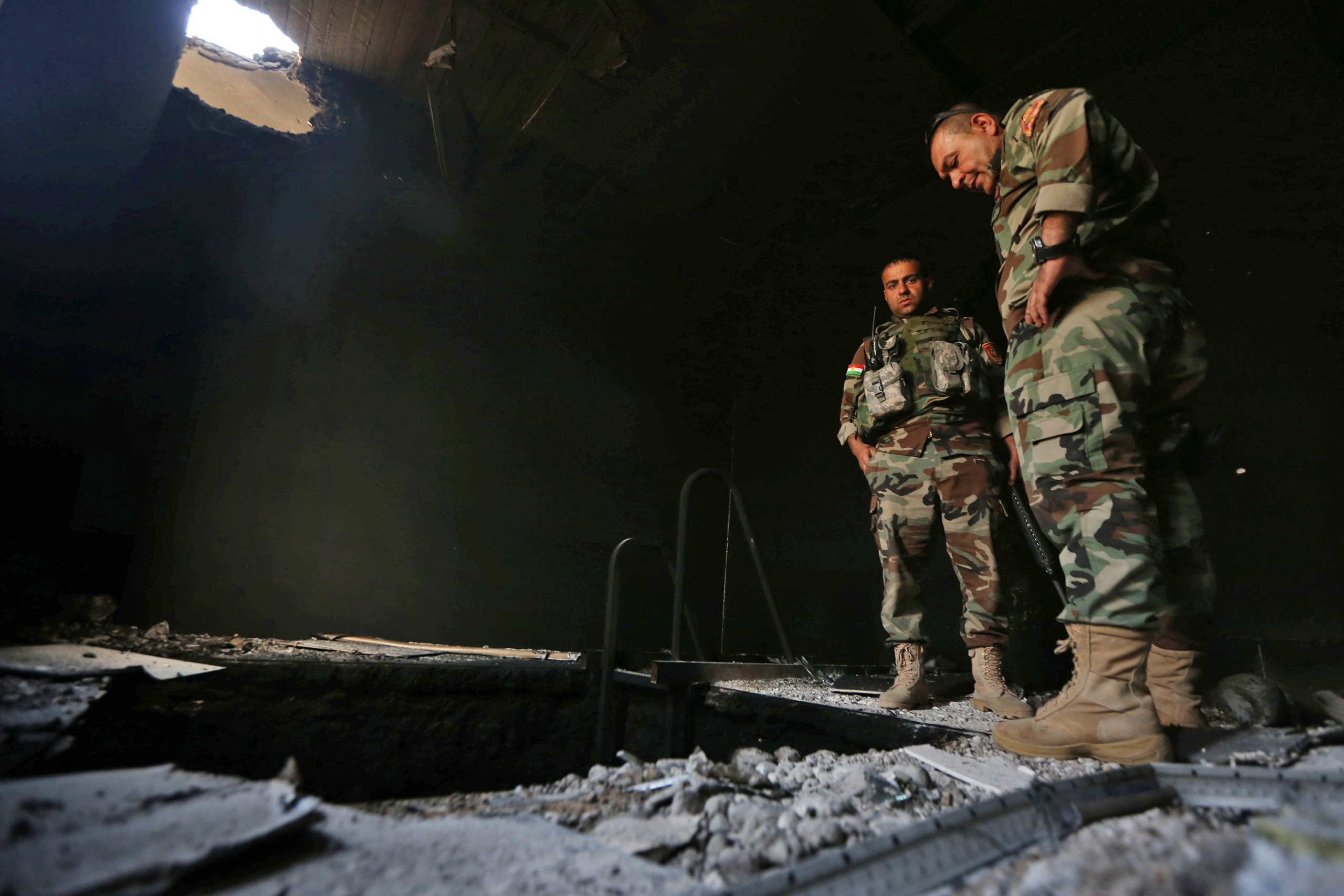 Kurdish Peshmerga forces inspect a tunnel inside a building in the Shaqouli village, about 35 kilometers east of Mosul, after they've recaptured it from ISIS on Oct. 18, 2016.