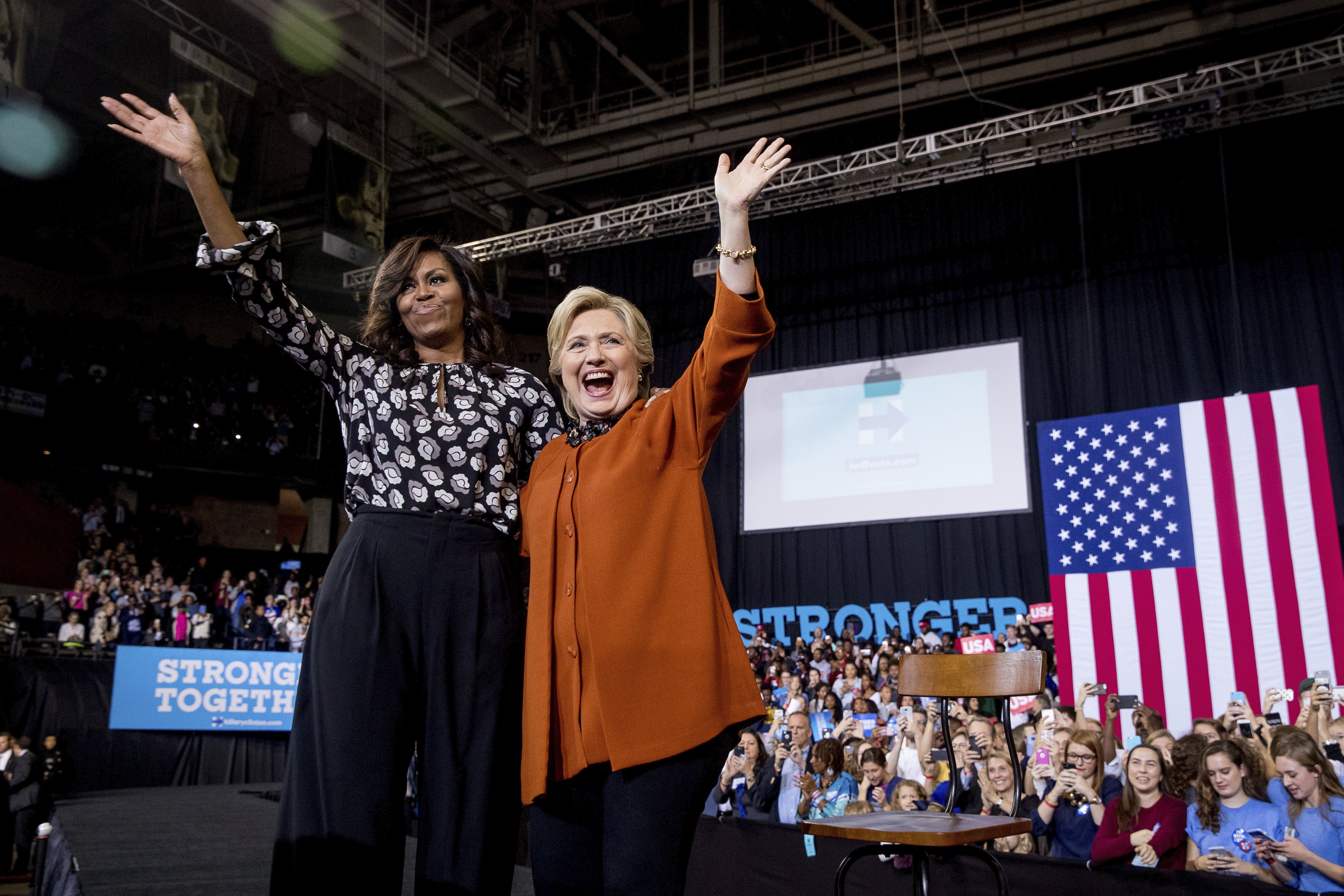 Michelle Obama and Hillary Clinton wave together after speaking at a campaign rally in Winston-Salem, NC, on Oct. 27, 2016.