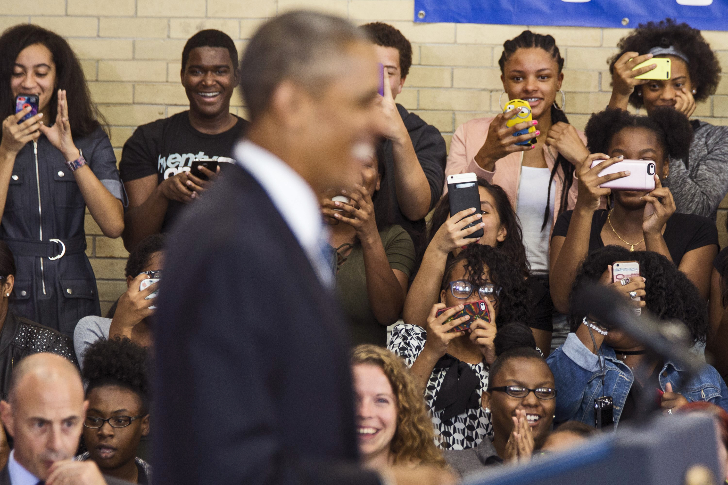 Obama smiles as students take photos on their cell phones during a speech at Benjamin Banneker Academy High School in Washington, on Oct. 17, 2016.