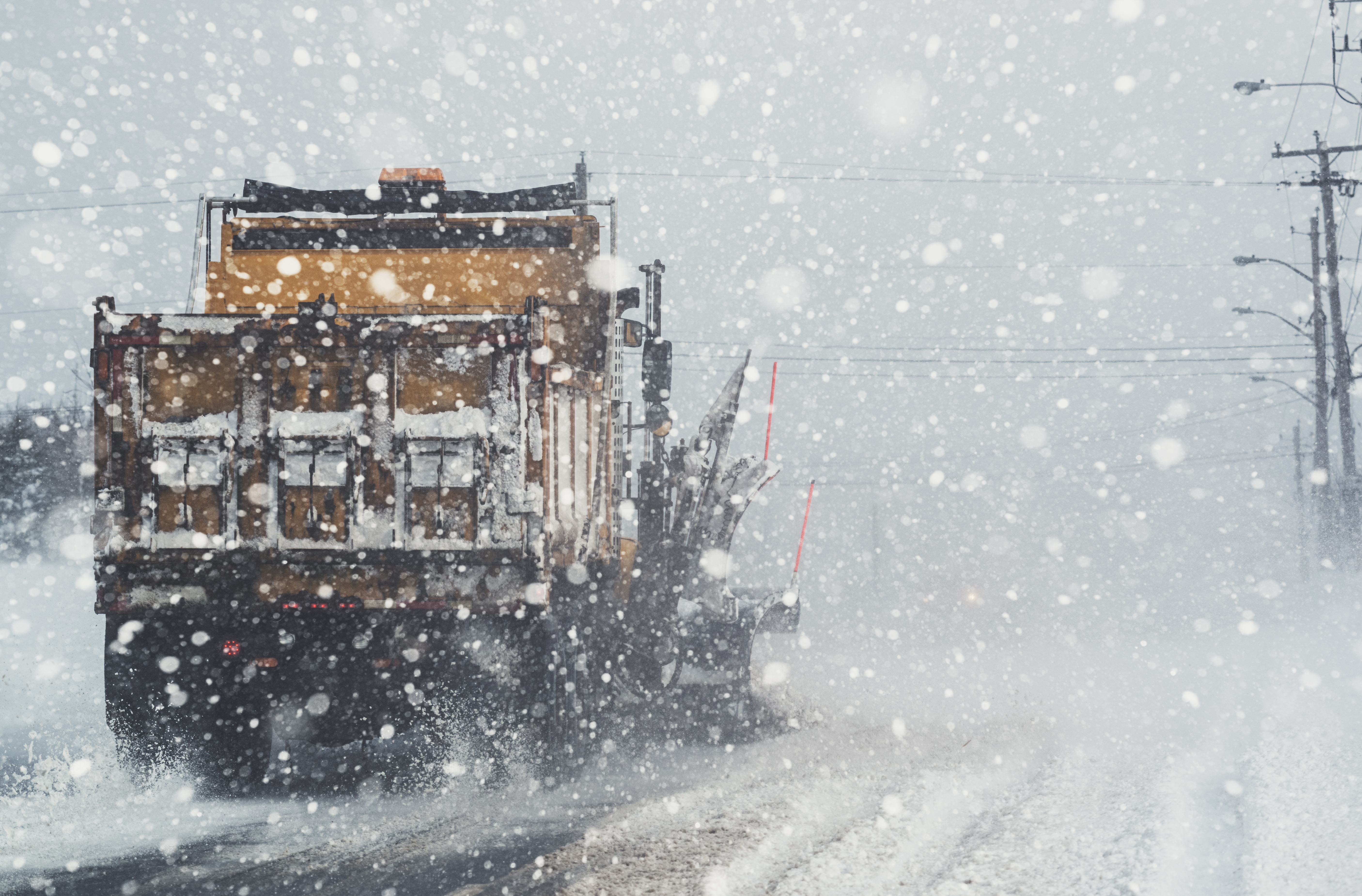 A snowplow clears a city street during a very heavy snowfall.